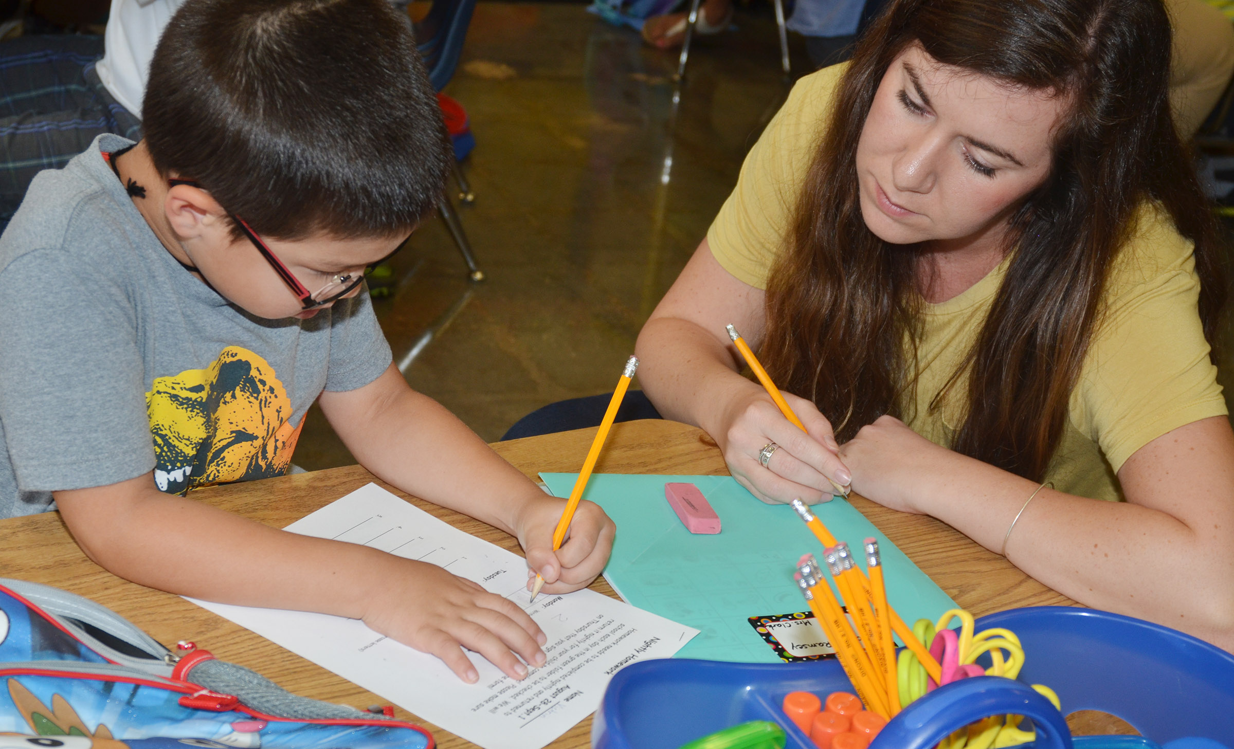 CES guidance assistant Courtney Mills helps kindergartener Victrin Ramsey with his homework at Wings Express.