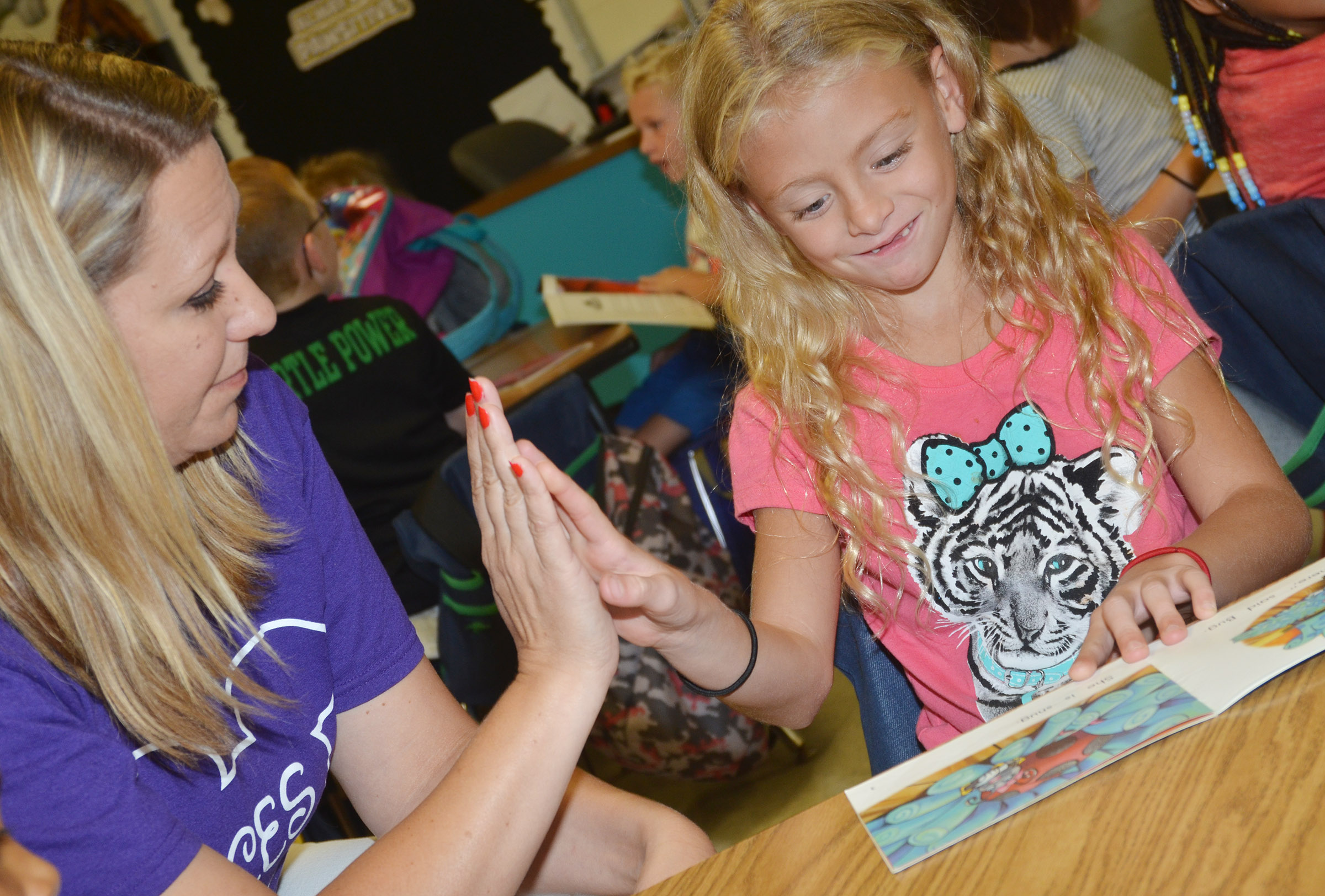 CES first-grade teacher Amanda Greer high-fives first-grader Aliyah Litsey as she reads during the Wings Express program.