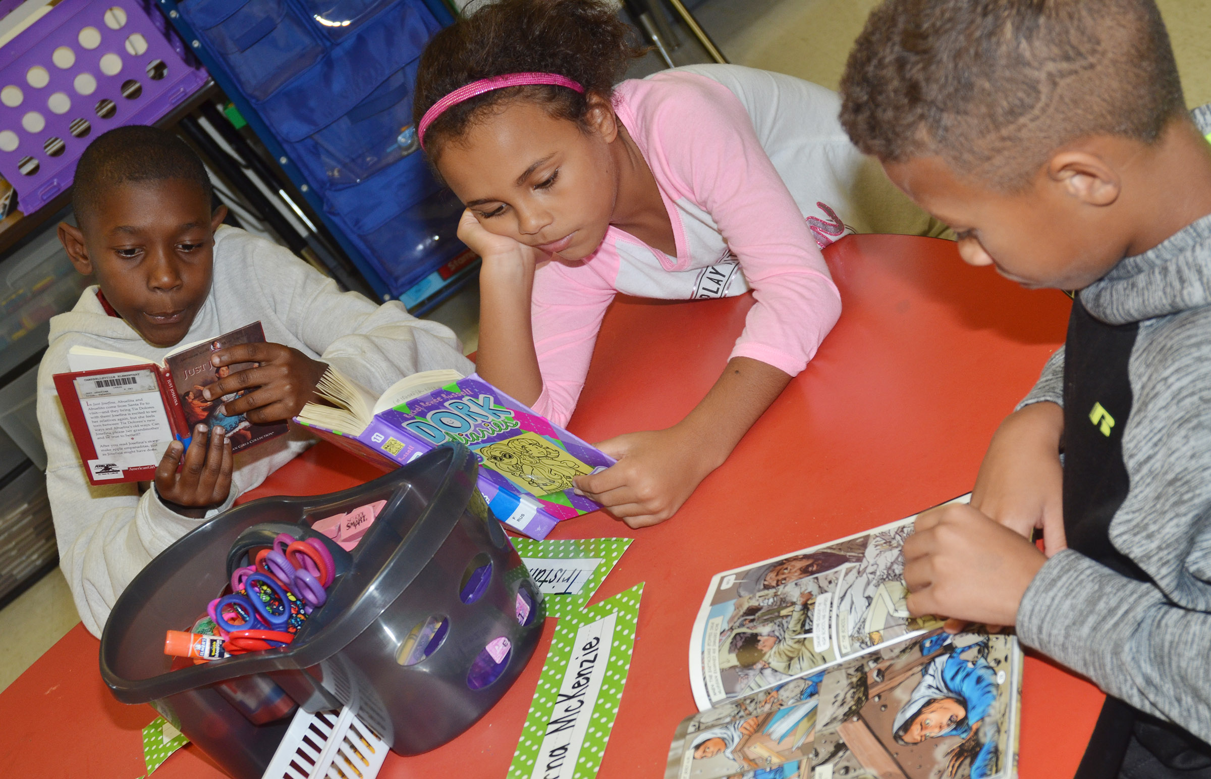 From left, CES third-graders Jaron Johnson, Braelyn Taylor and Rajon Taylor read together.