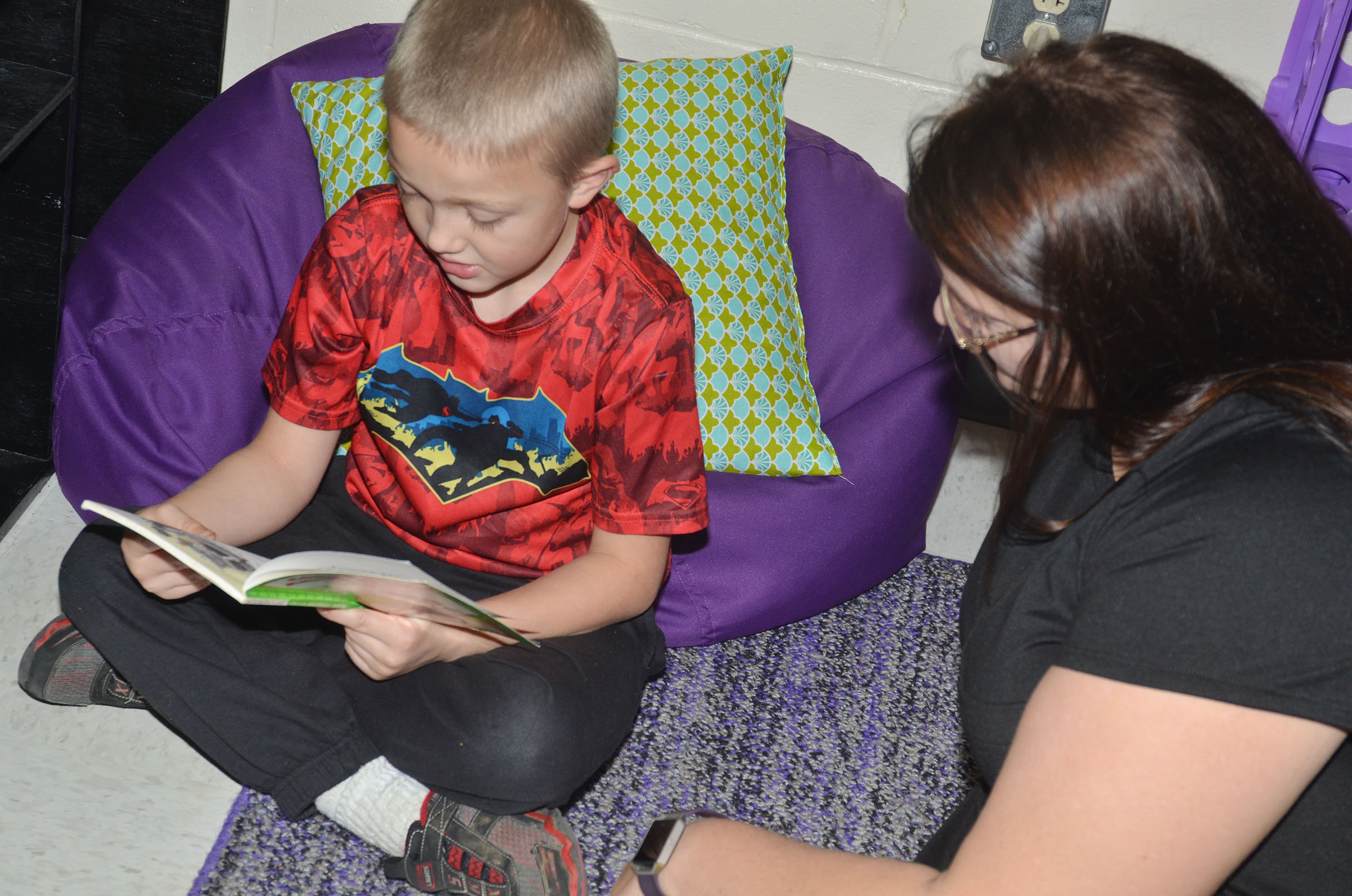 CES second-grader Trenton Harris reads with Wings Express assistant Miriah Cox.