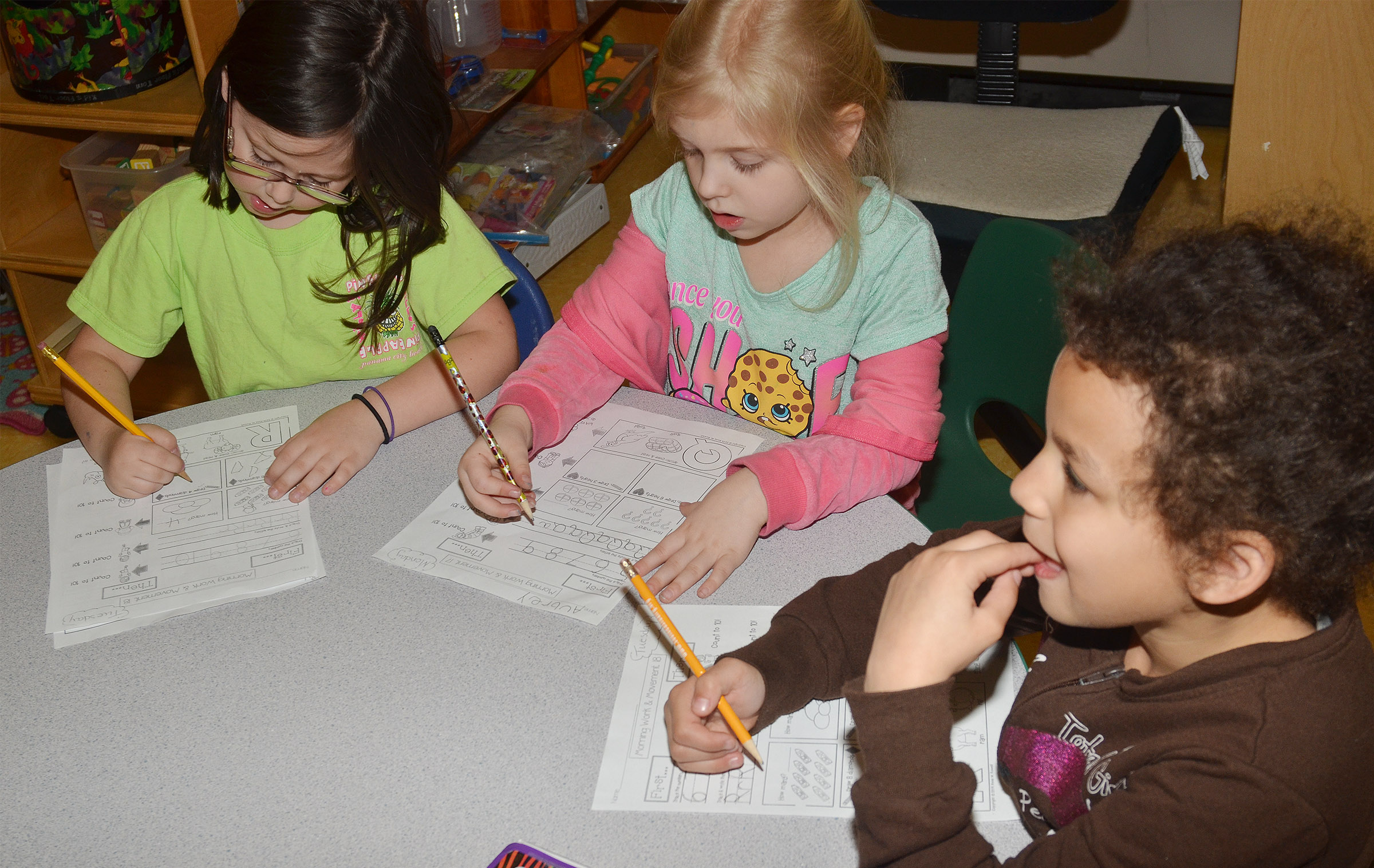 From left, CES kindergarteners Trinity Clark, Aubrey Novak and Aleeya Spaulding work on their homework.