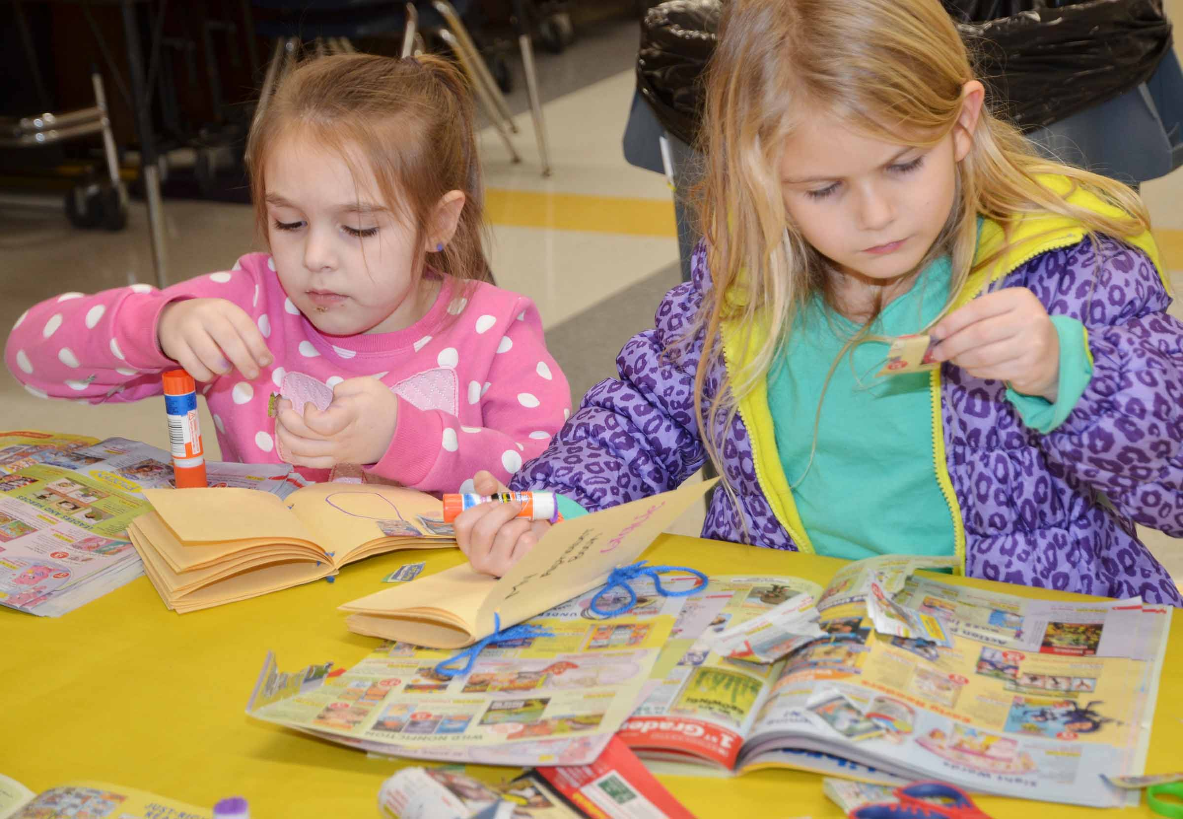 CES kindergarteners Aubrey Allen, at left, and Gracie Gebler cut out words for their alphabet book.