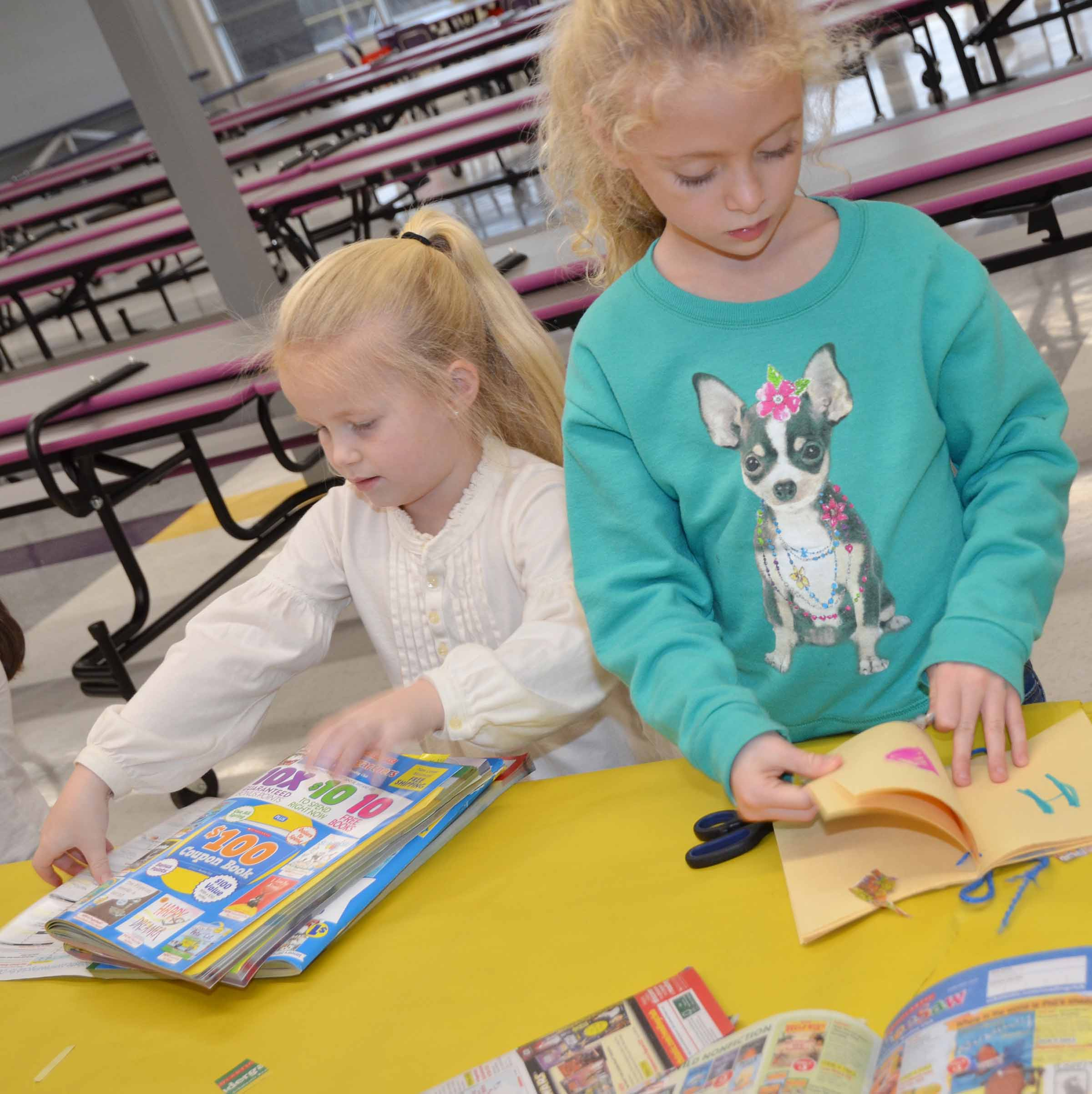CES kindergarteners Lillie Judd, at left, and Aliyah Litsey cut out words and pictures for their alphabet book.