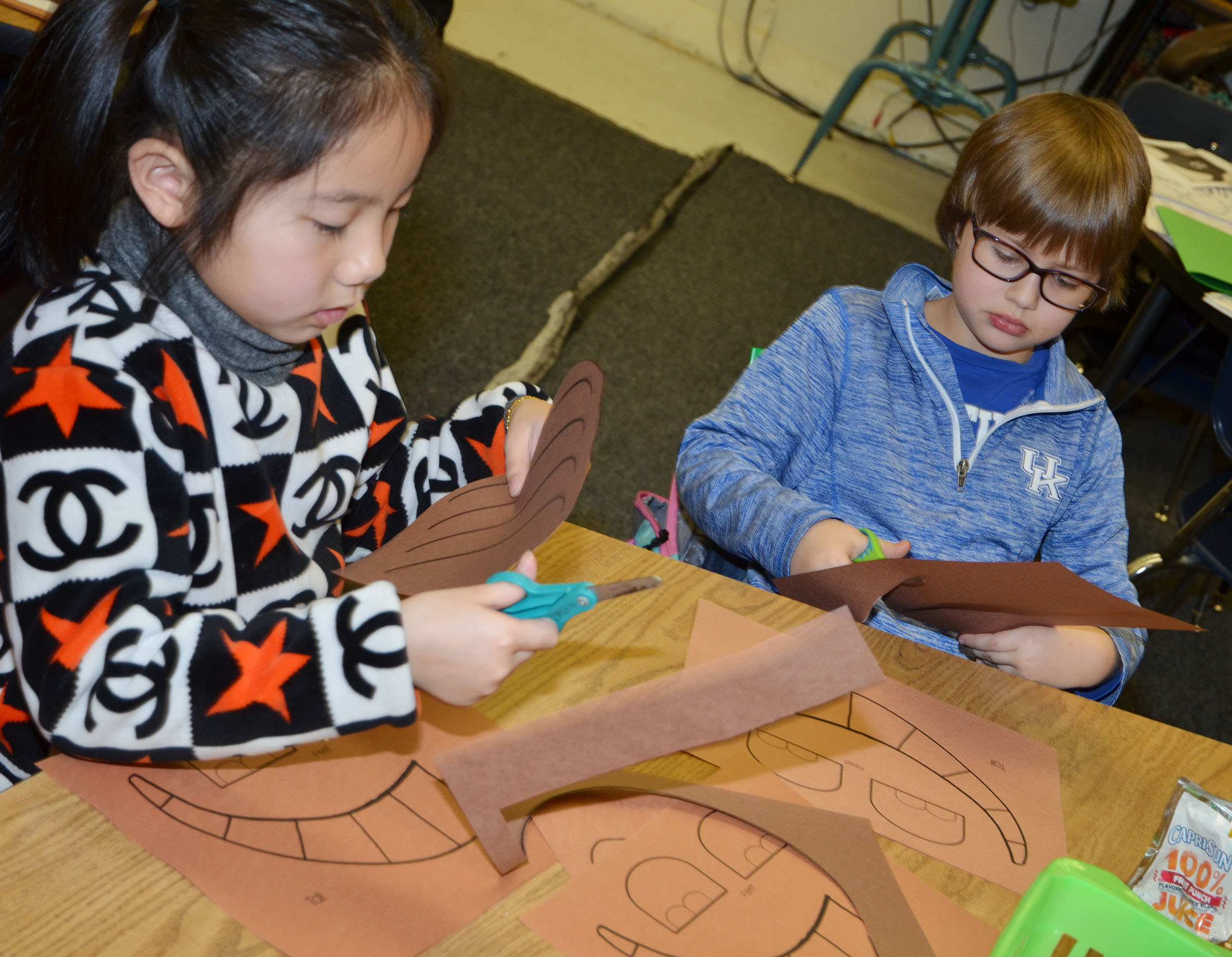 CES first-graders Tina Jiang, at left, and Addelyn Dooley cut out the pieces of their armadillo to glue together.