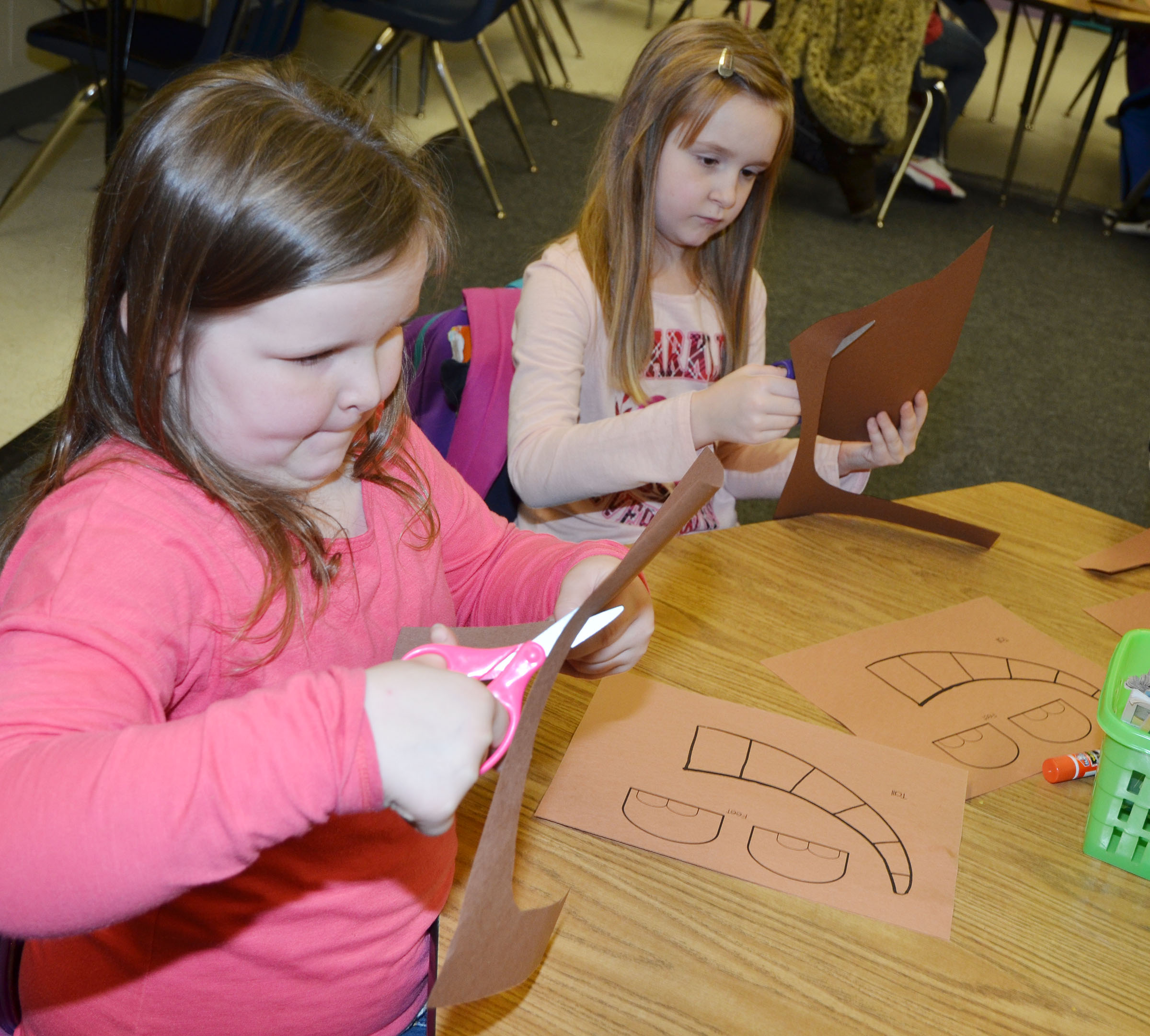 CES first-graders Kierra Maupin, at left, and Gracie Murphy cut out their pieces of their armadillo to glue together.