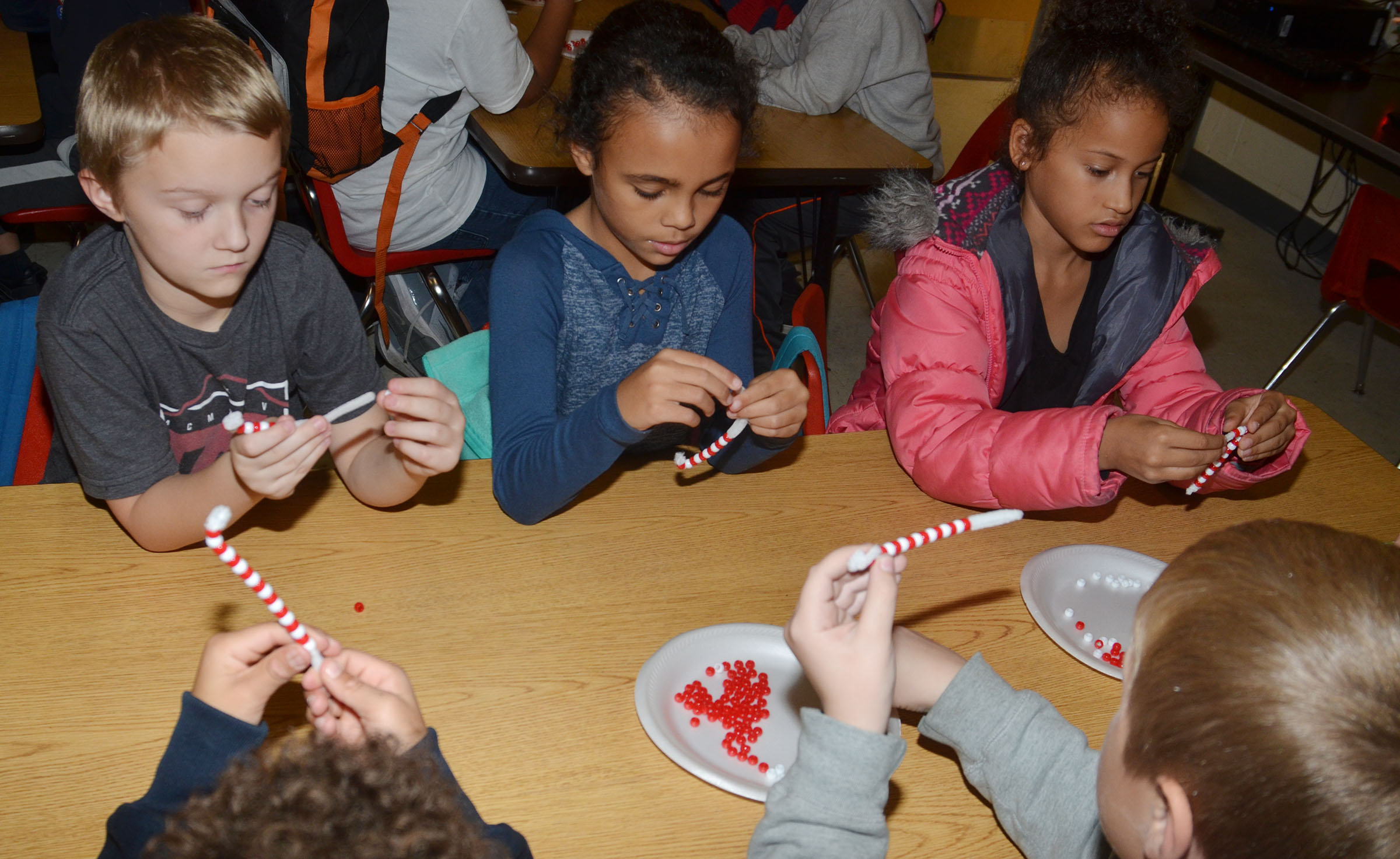 CES second-graders Camren Skaggs, Braelyn Taylor and Yazlyn Sutton add beads to their candy cane ornaments.