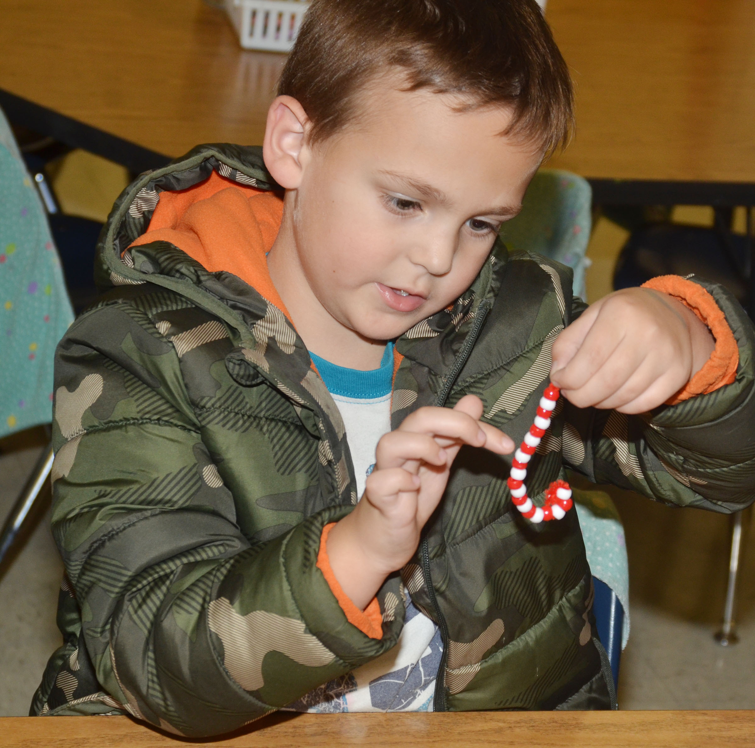 CES first-grader Brendan Martin counts how many beads he used to make his ornament.