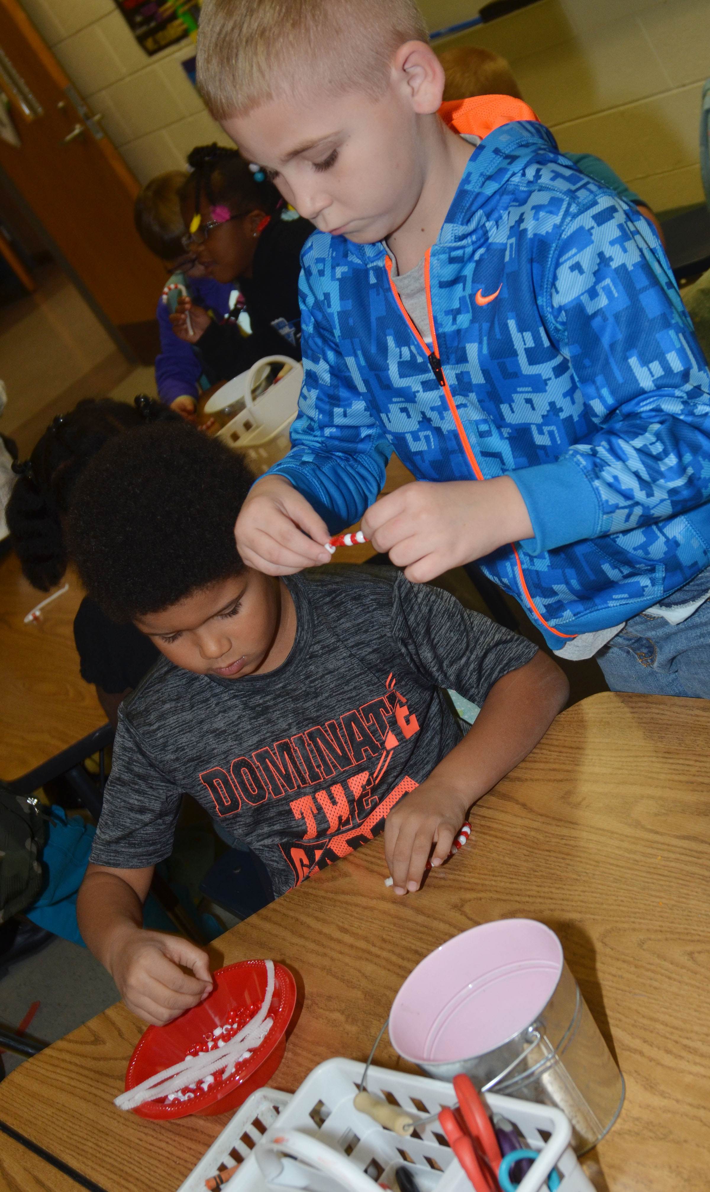 CES first-grader Navon Copeland, at left, and second-grader Joseph Greer make their candy cane ornaments.