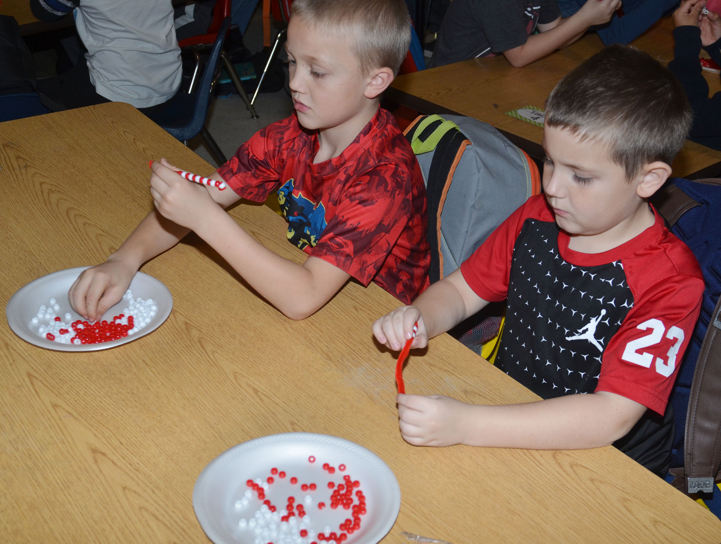 CES second-grader Trenton Harris, at left and Seamus Huber make their candy cane ornaments.
