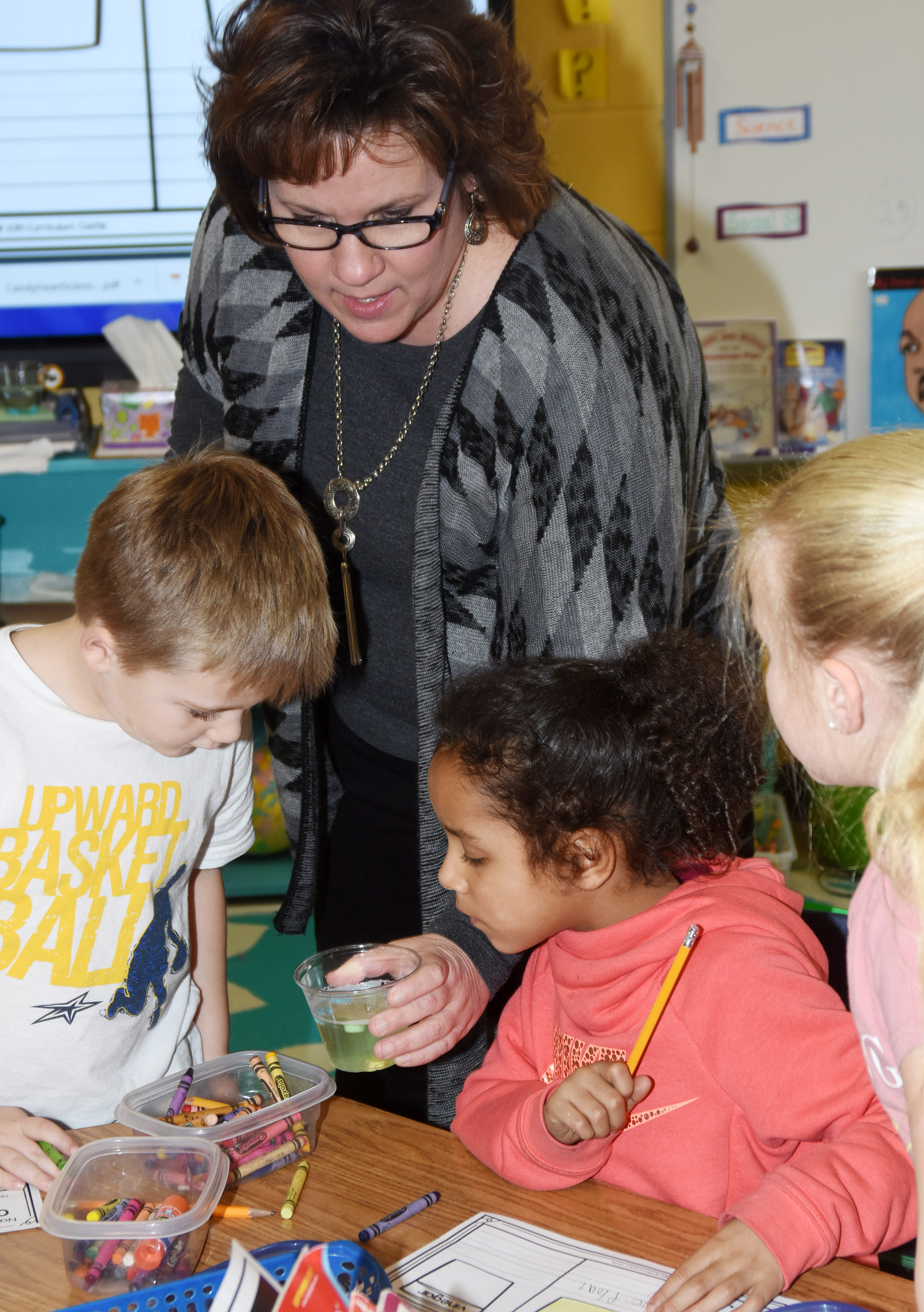 CES teacher Tracey Rinehart shows, from left, kindergartener Jacob Sandidge and first-graders Kylei Thompson and Lillie Judd what happens to candy hearts as they soak in water.