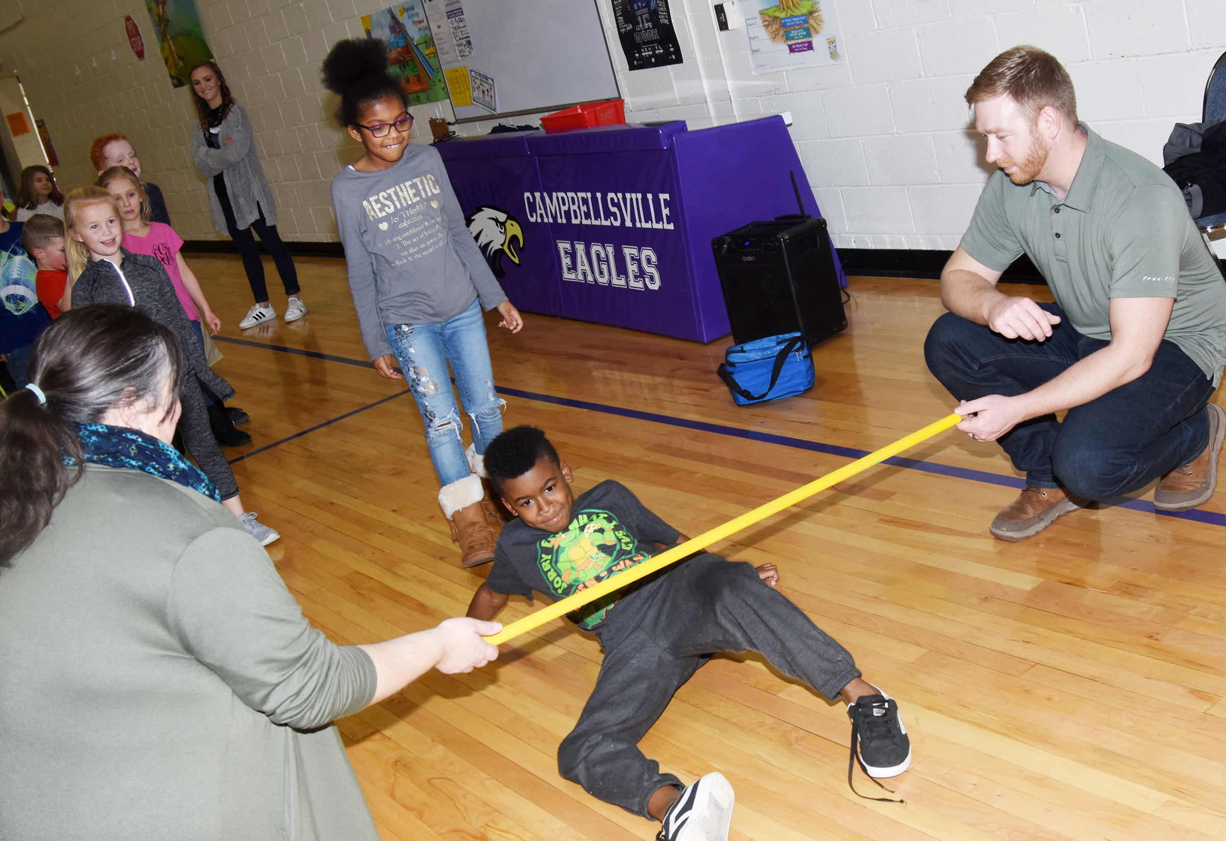 CES third-grader Kae'vin Spaulding limbos, with help from Campbellsville/Taylor County Chamber of Commerce Board members Latasha Bell and Luke Lawless.