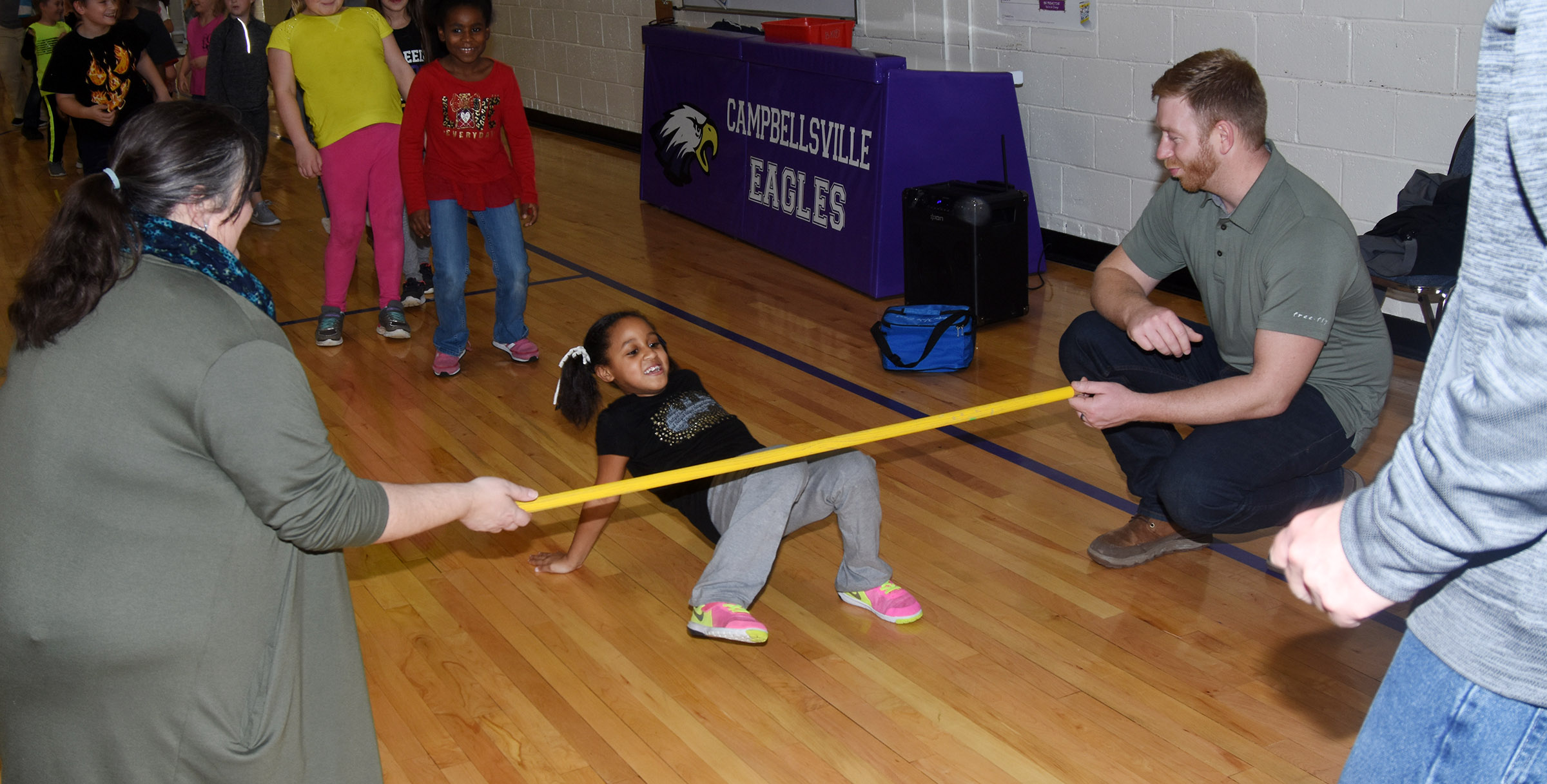 CES second-grader Kadance Ford limbos, with help from Campbellsville/Taylor County Chamber of Commerce Board members Latasha Bell and Luke Lawless.