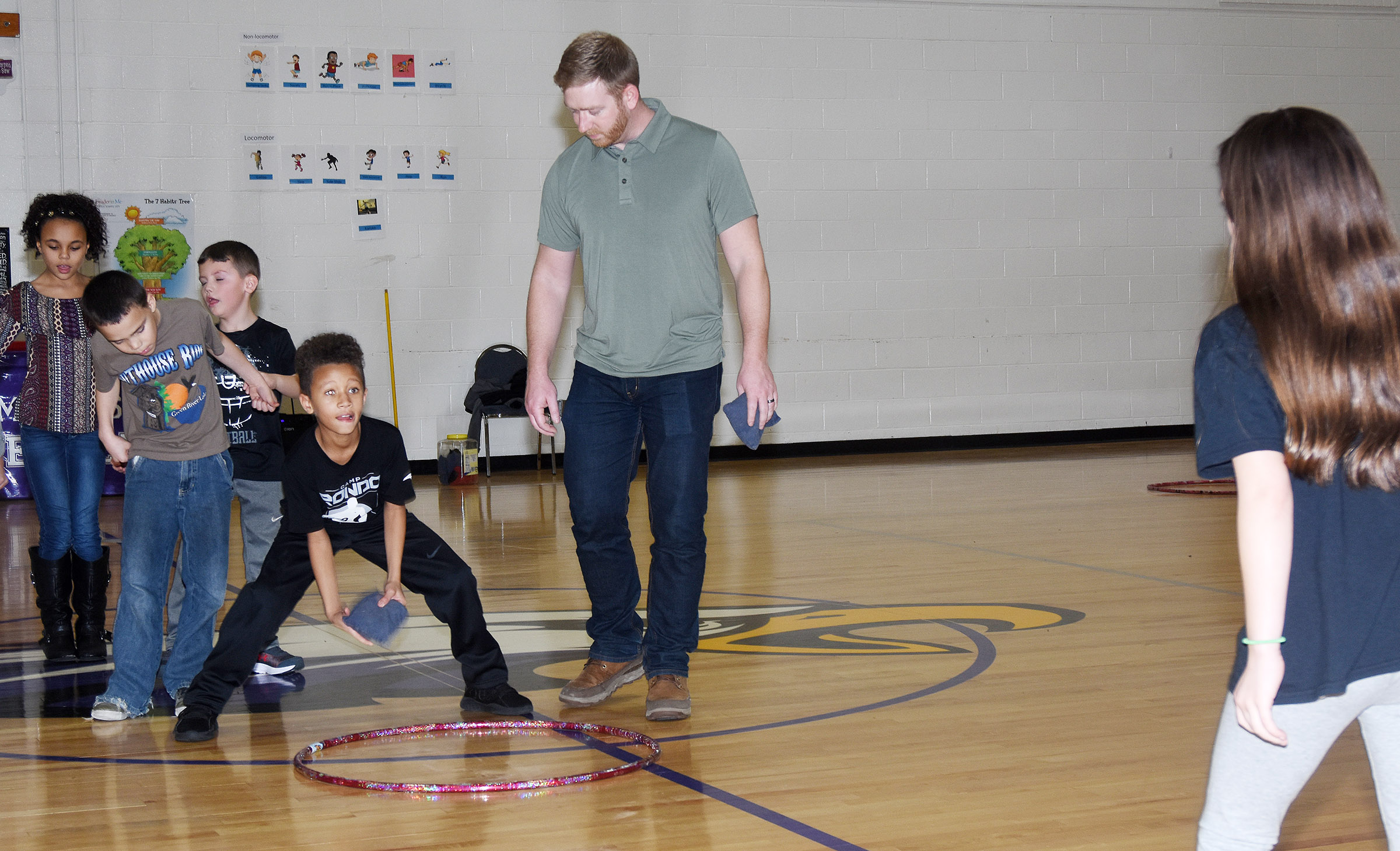 CES third-grader Rajon Taylor tosses a bean bag, with help from Campbellsville/Taylor County Chamber of Commerce Board member Luke Lawless.