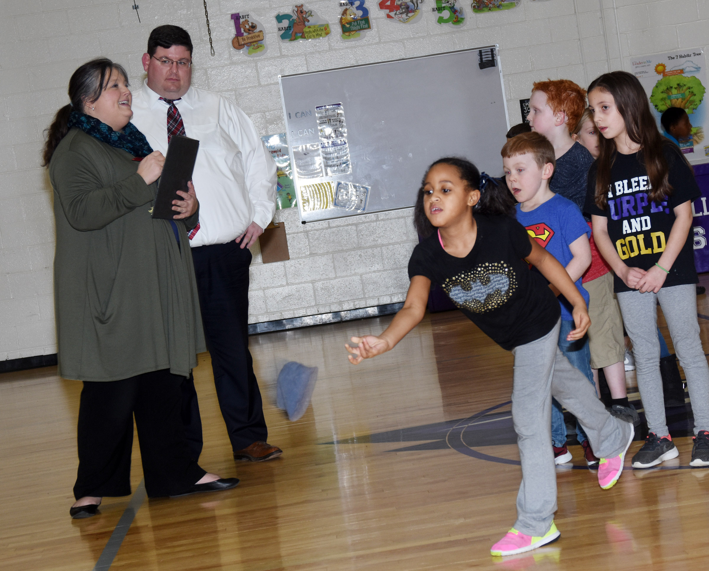 CES second-grader Kadance Ford throws a bean bag, as Campbellsville/Taylor County Chamber of Commerce Board members Latasha Bell and Jeremy Wood watch.