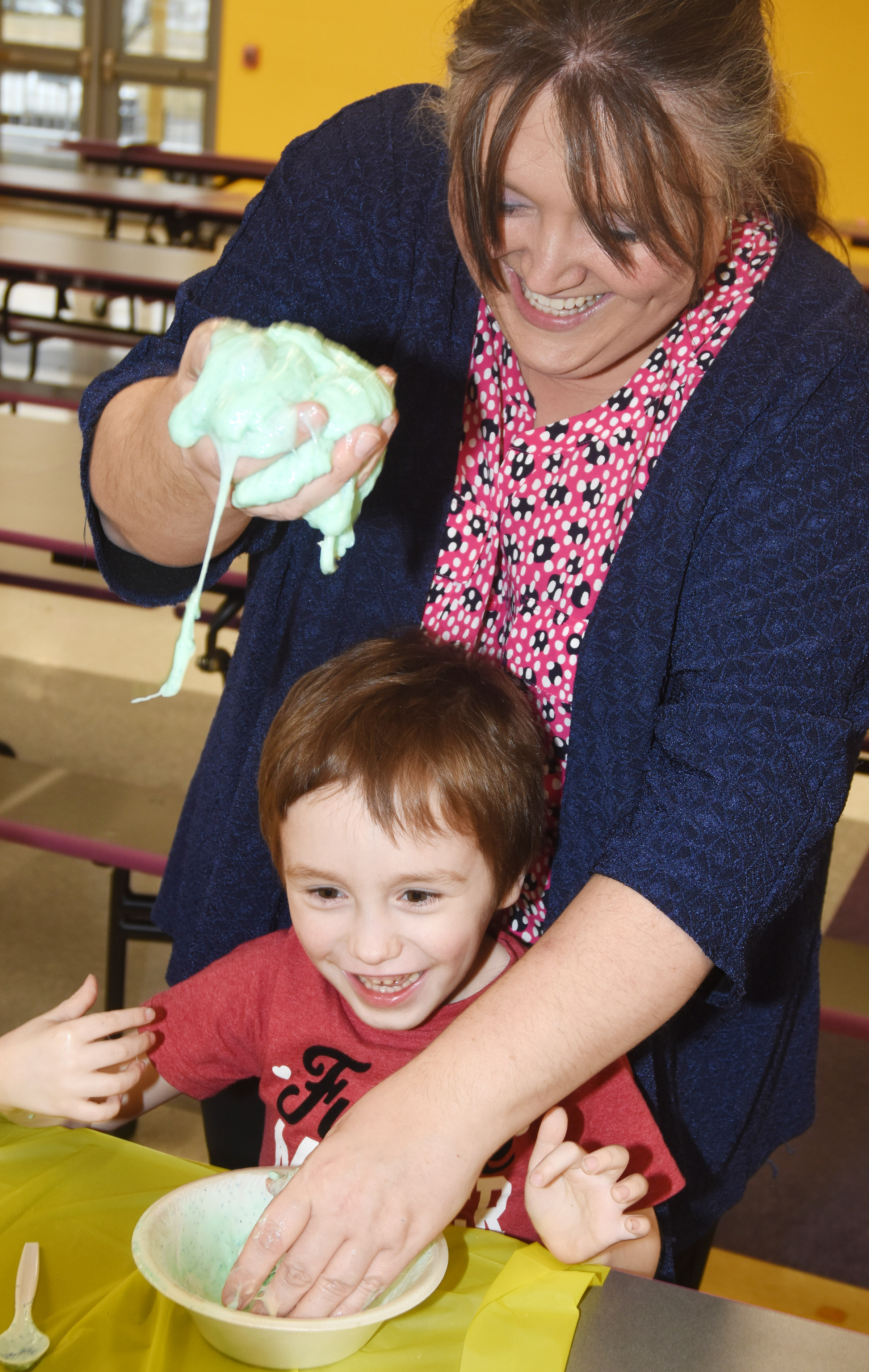 CES kindergartener Joshua Dickens picks up his slime, with some help from Campbellsville/Taylor County Chamber of Commerce Board member Latasha Bell.