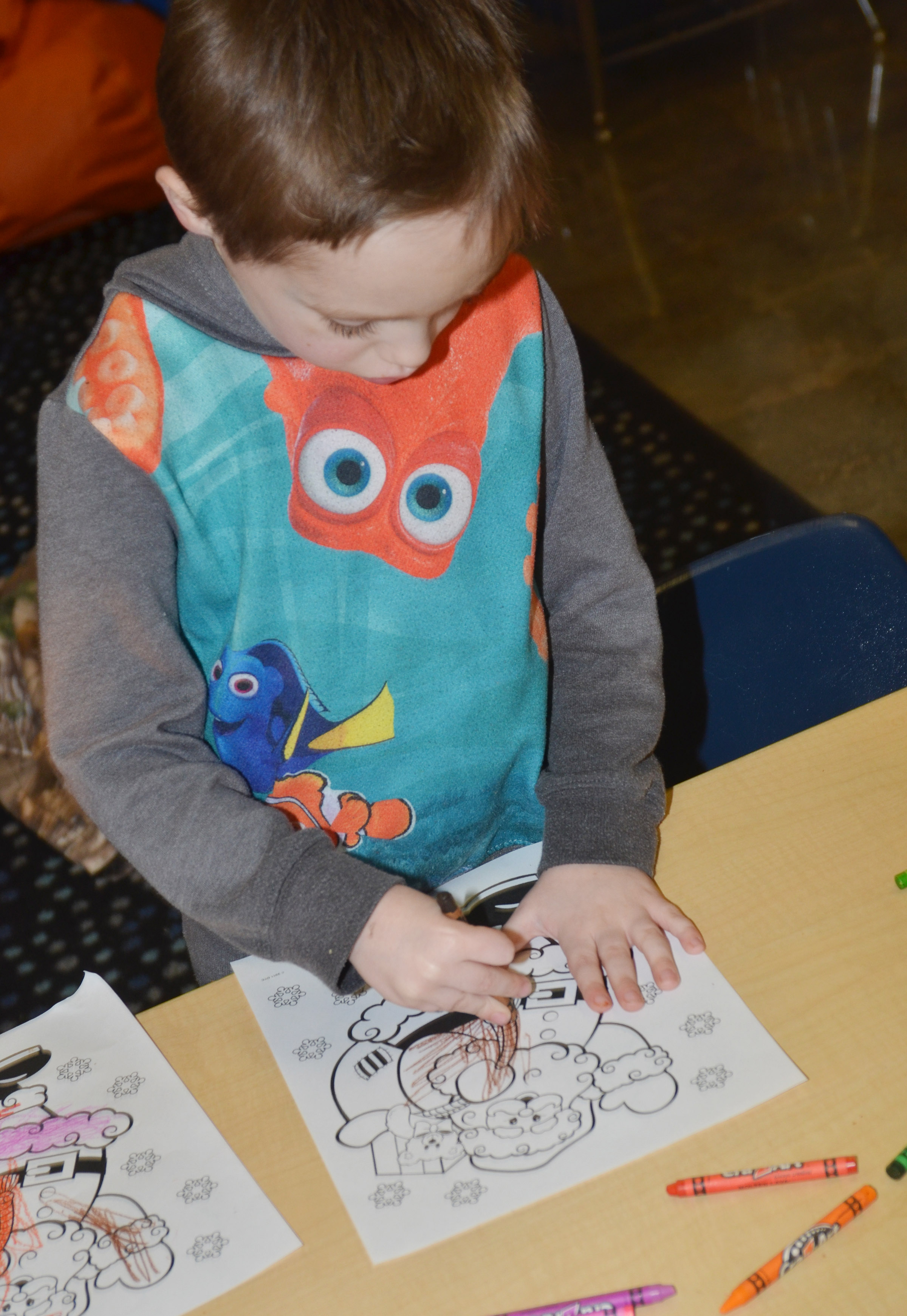 CES kindergartener Joshua Dickens colors a Christmas page during a party for Wings Express students.