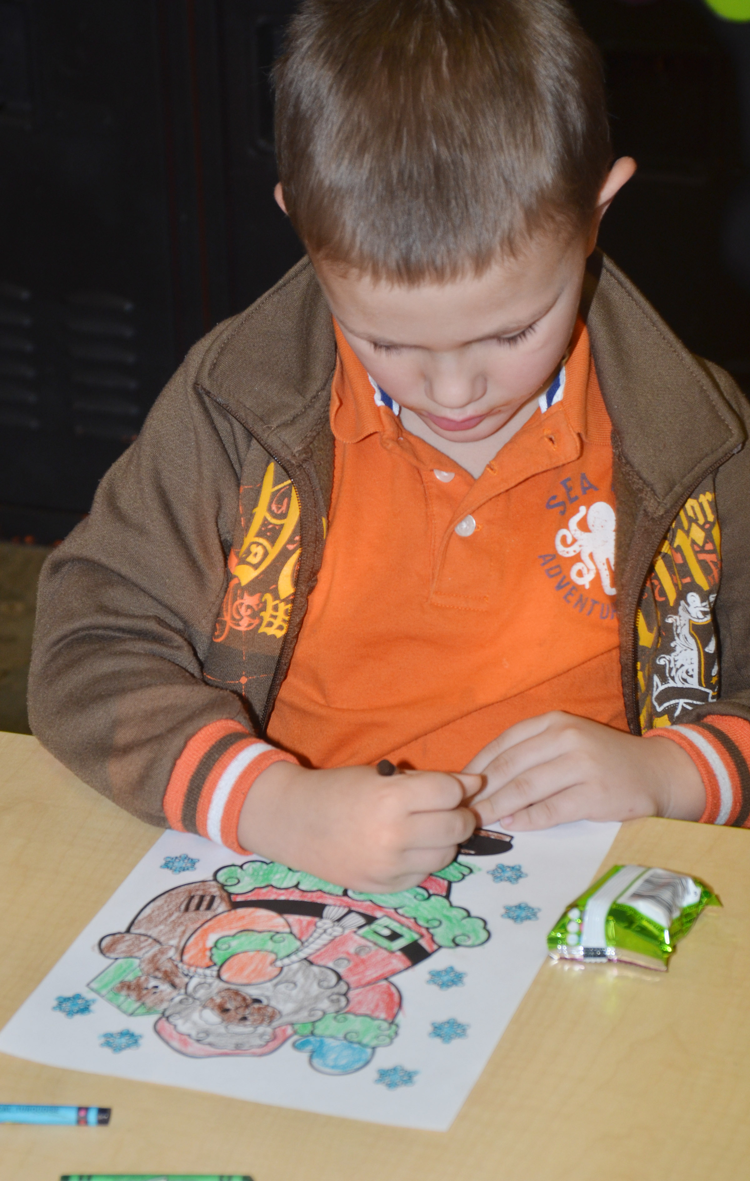 CES kindergartener Dawson Morton colors a Christmas page during a party for Wings Express students.