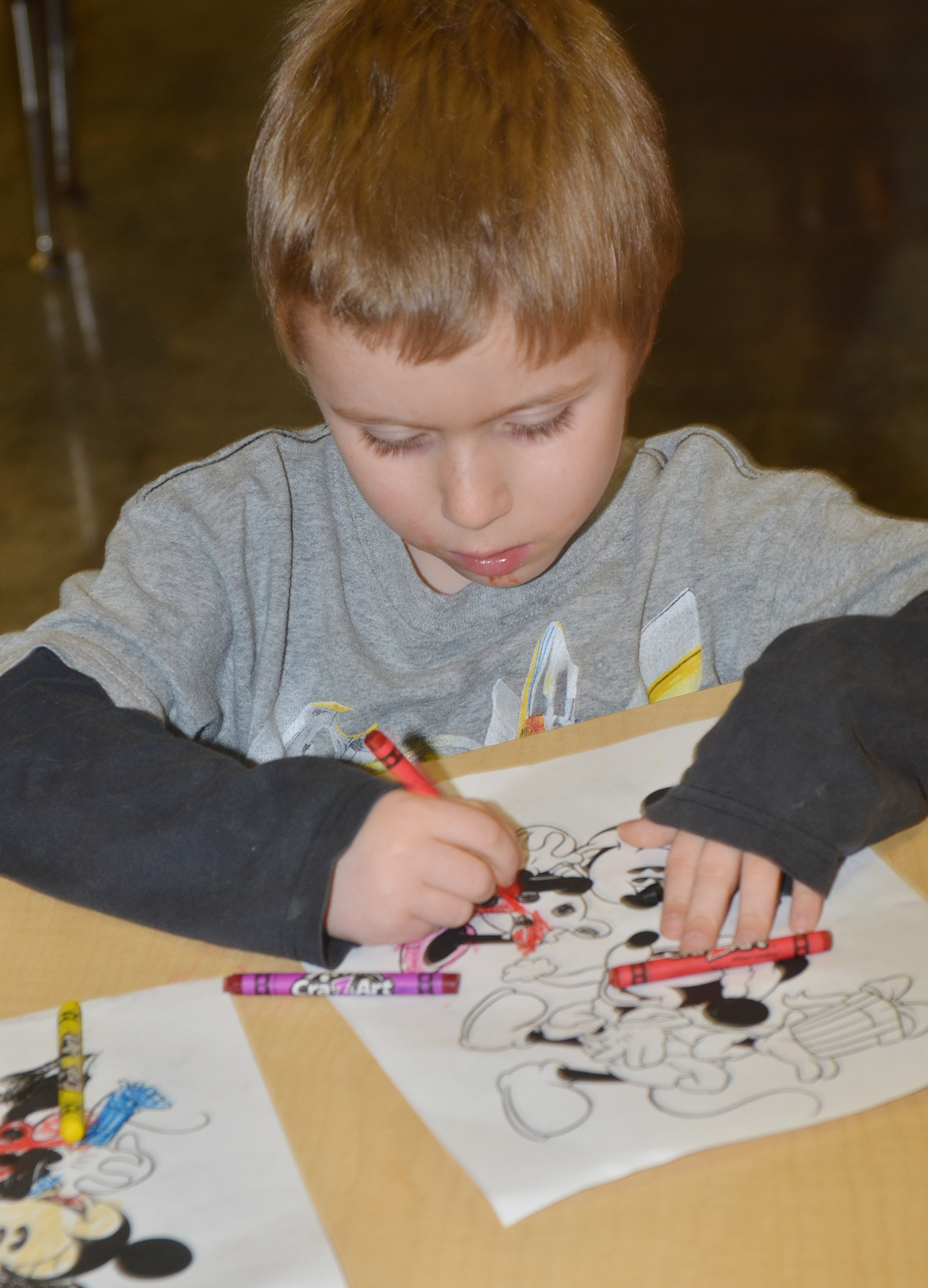 CES kindergartener Alex Newcomb colors a Christmas page during a party for Wings Express students.
