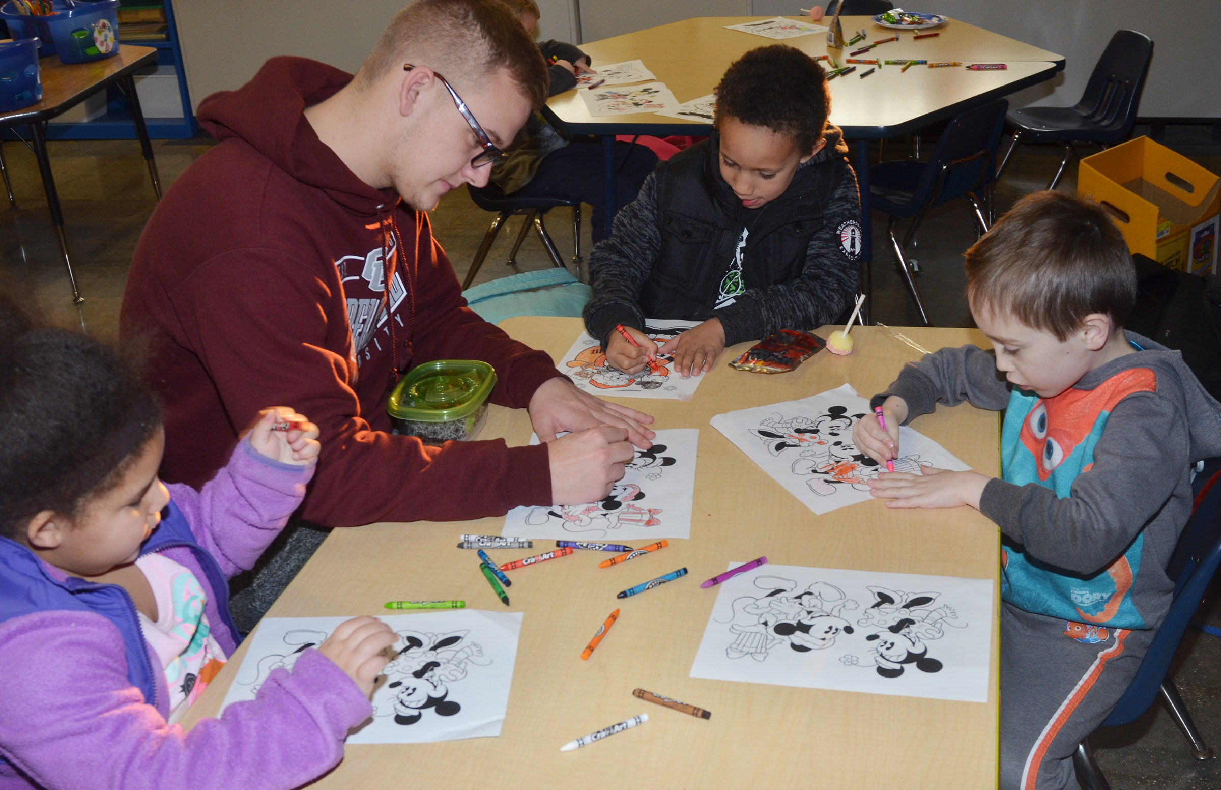 CES kindergarteners, from left, Tatum Hoskins, Jaxon Williams and Joshua Dickens color with Campbellsville University education student Brandon Rioux during a Christmas party for Wings Express students.