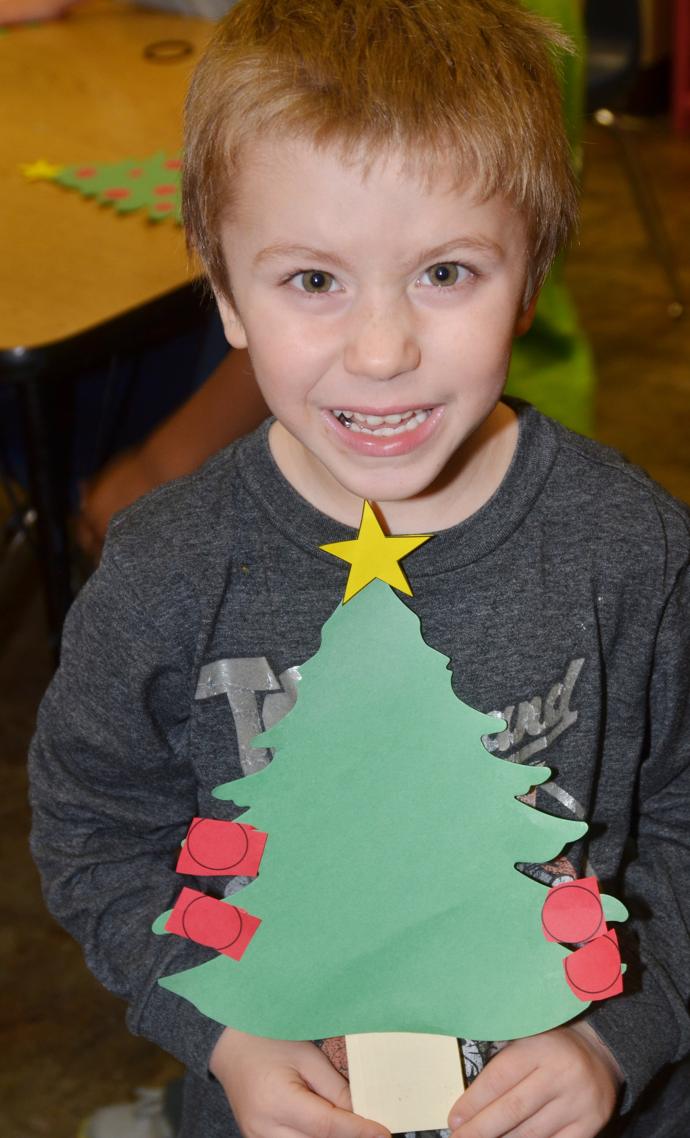 CES kindergartener Alex Newcomb holds his Christmas tree.