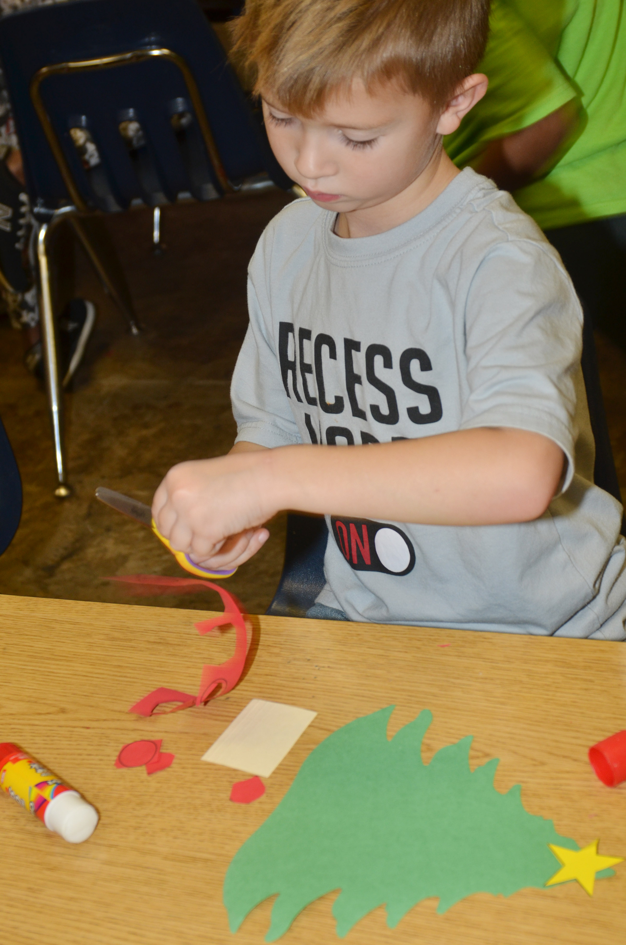 CES kindergartener Andrew Stout cuts out the pieces of his Christmas tree.