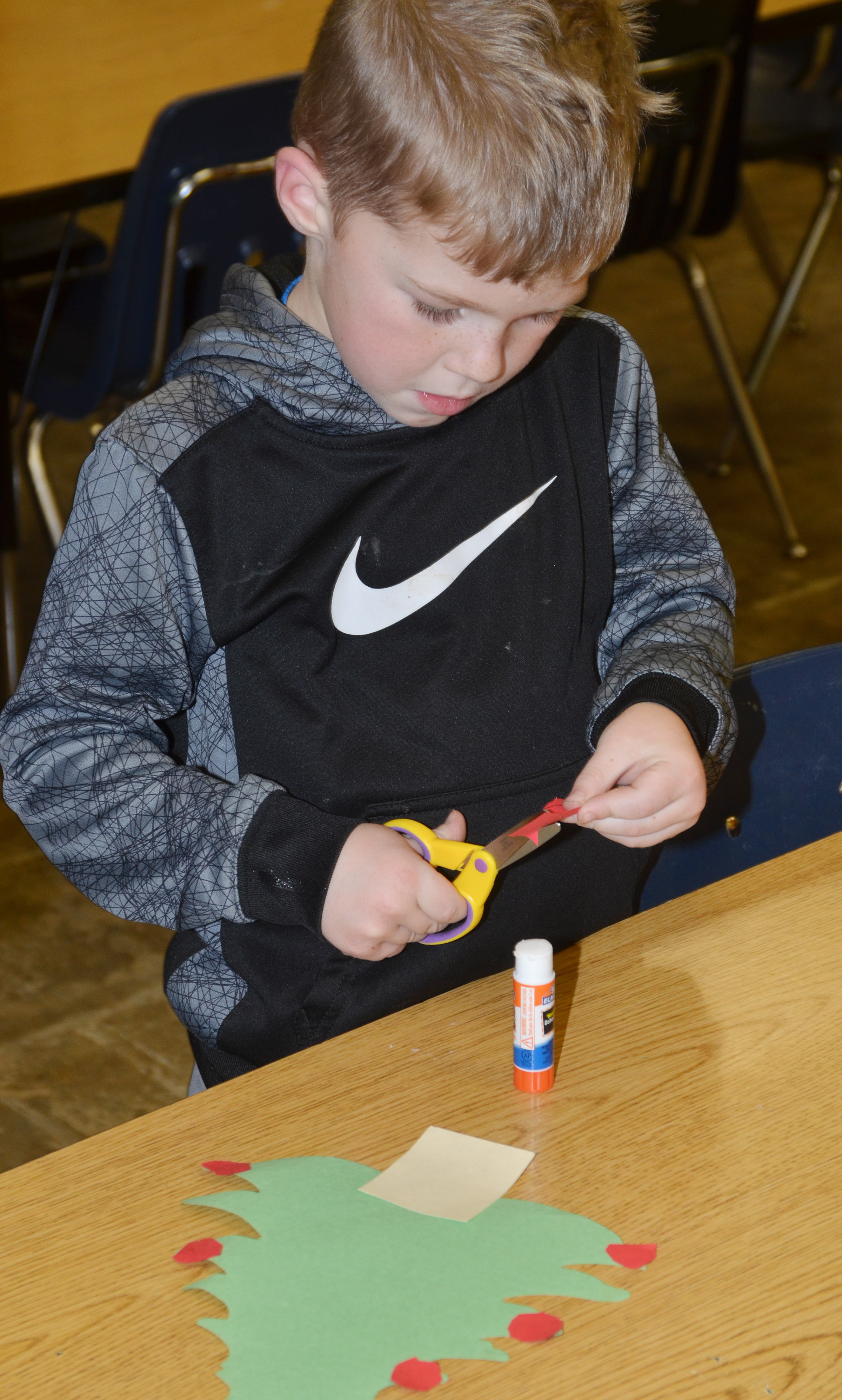CES kindergartener Landry Brown cuts out the pieces of his Christmas tree.