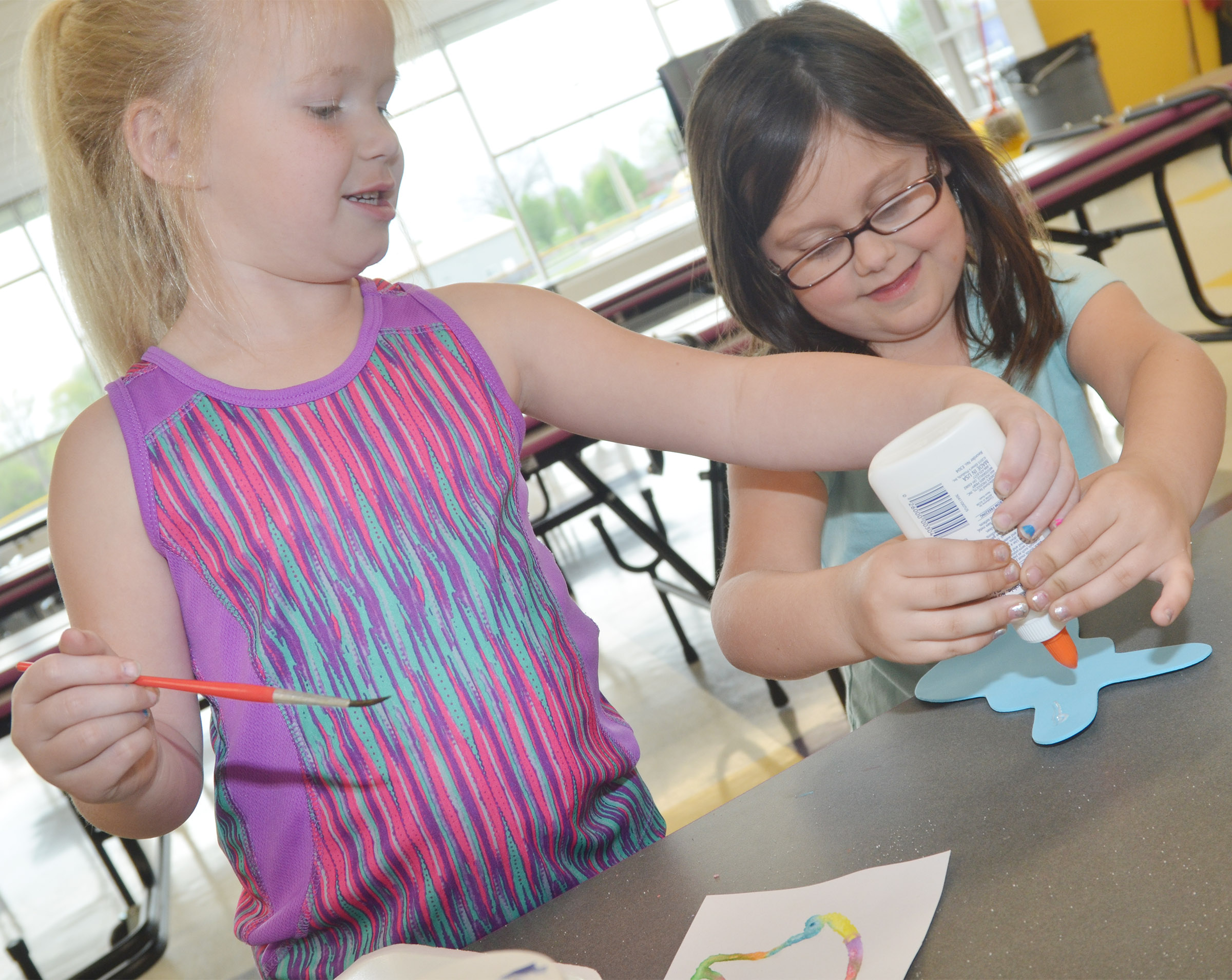CES kindergartener Lillie Judd helps classmate Trinity Clark create a design on her rabbit.