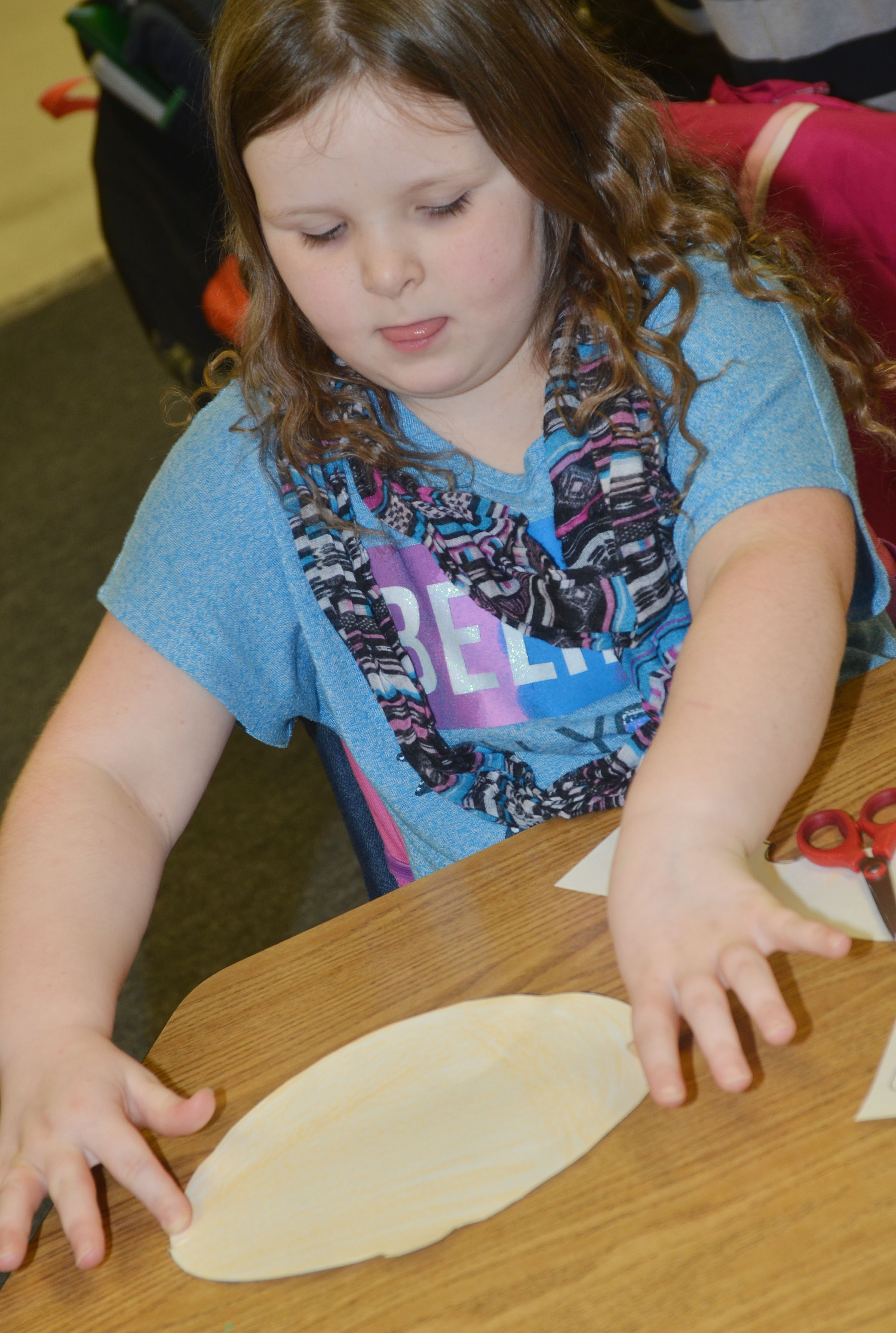 "CES first-grader Kierra Maupin glues together her ""Decibella"" face."