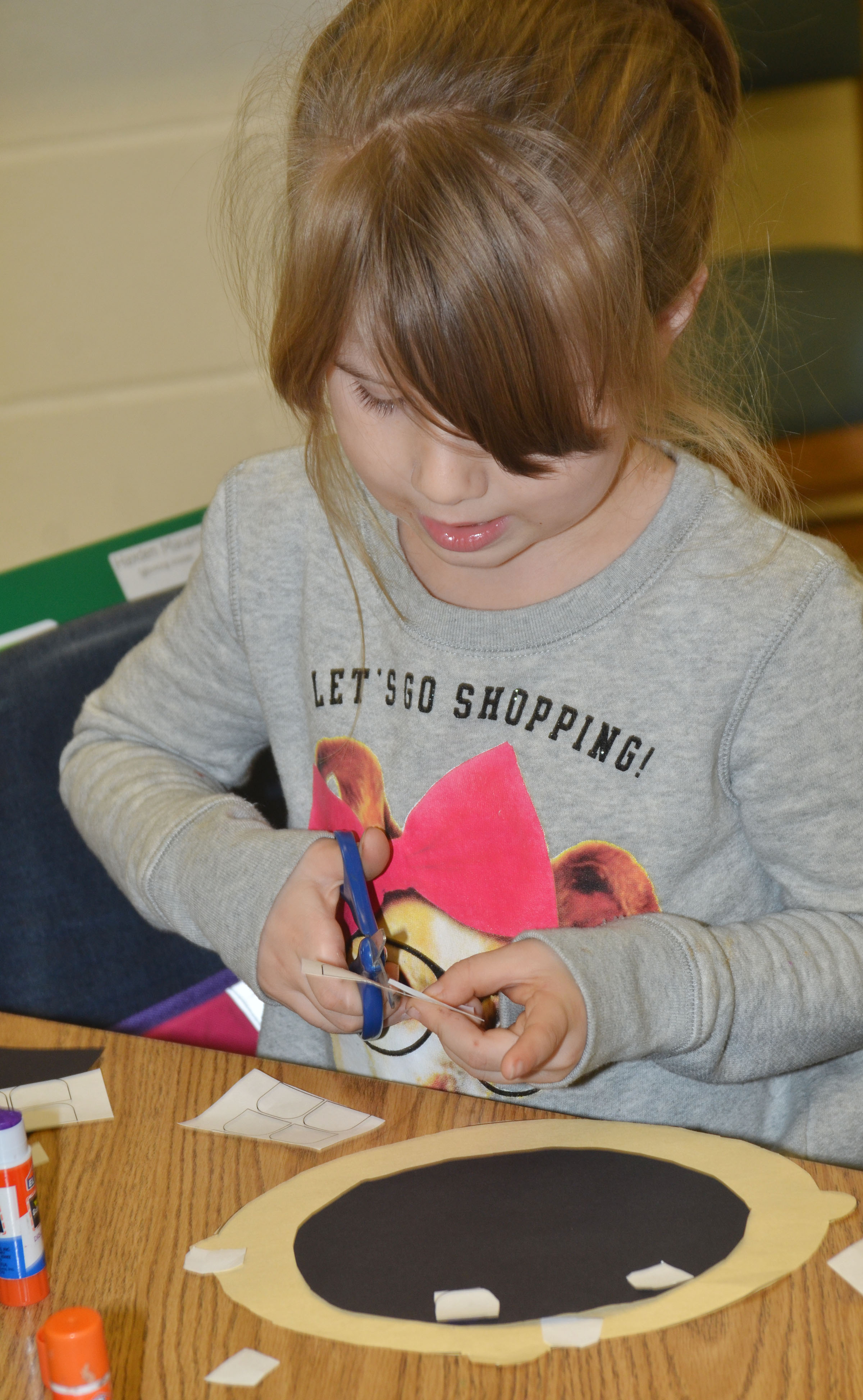 "CES first-grader Kenady Gabehart glues together her ""Decibella"" face."