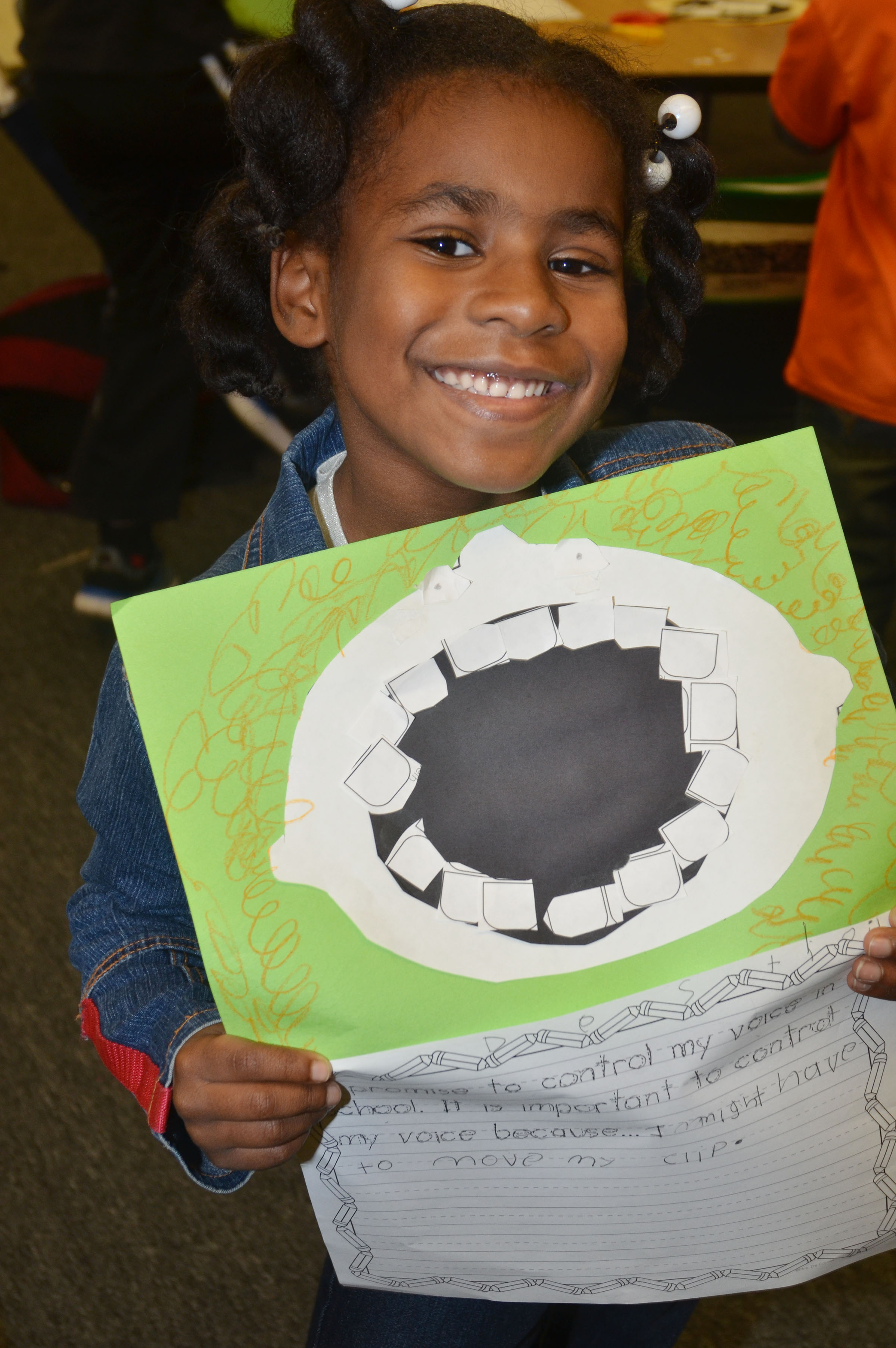 "CES first-grader Destini Gholston holds her finished ""Decibella"" face and writing."