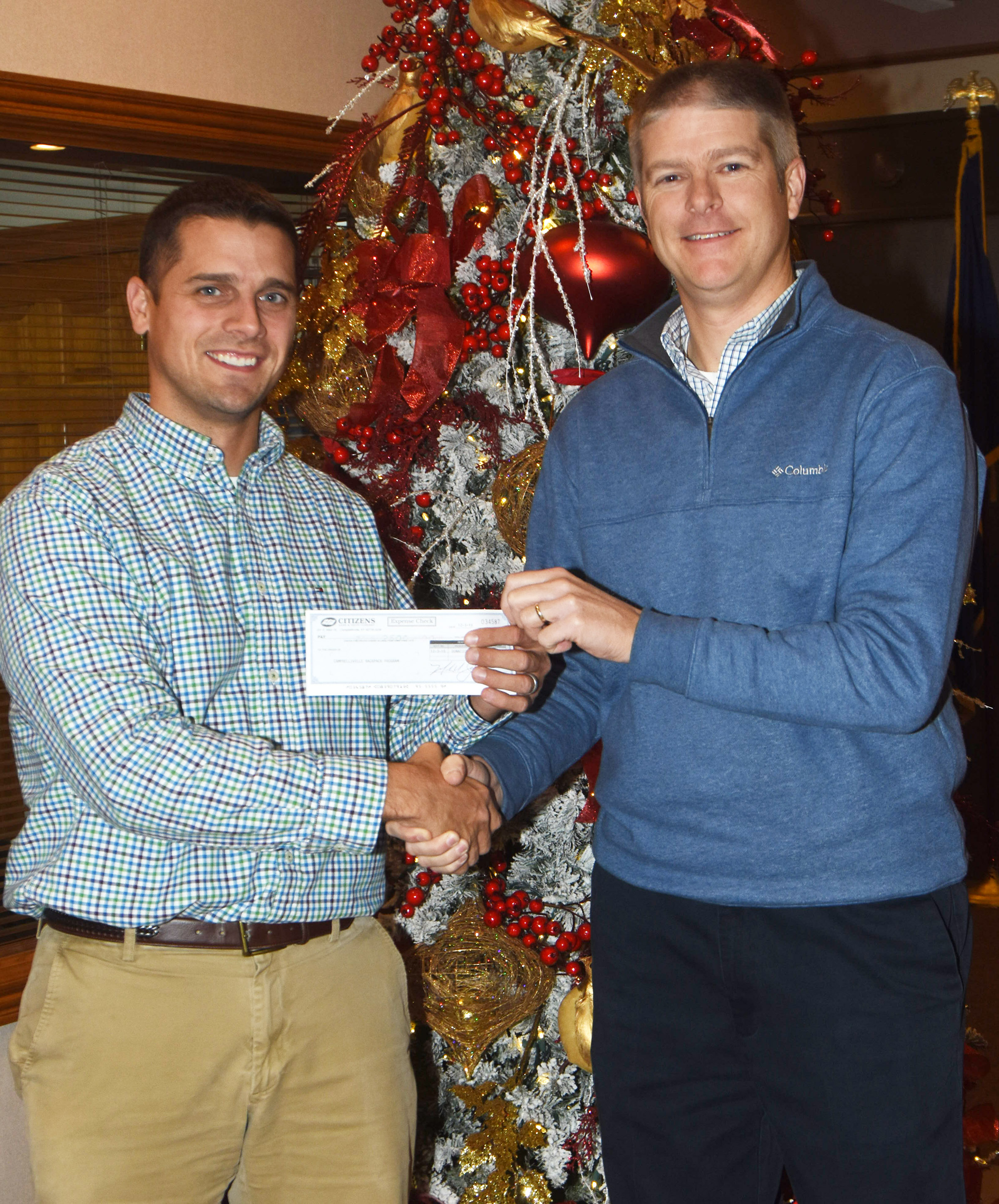 CES Wings Express Director Doug Holmes, at right, receives a $200 donation from Clark Howard, who works in marketing at Citizens Bank and Trust Co.