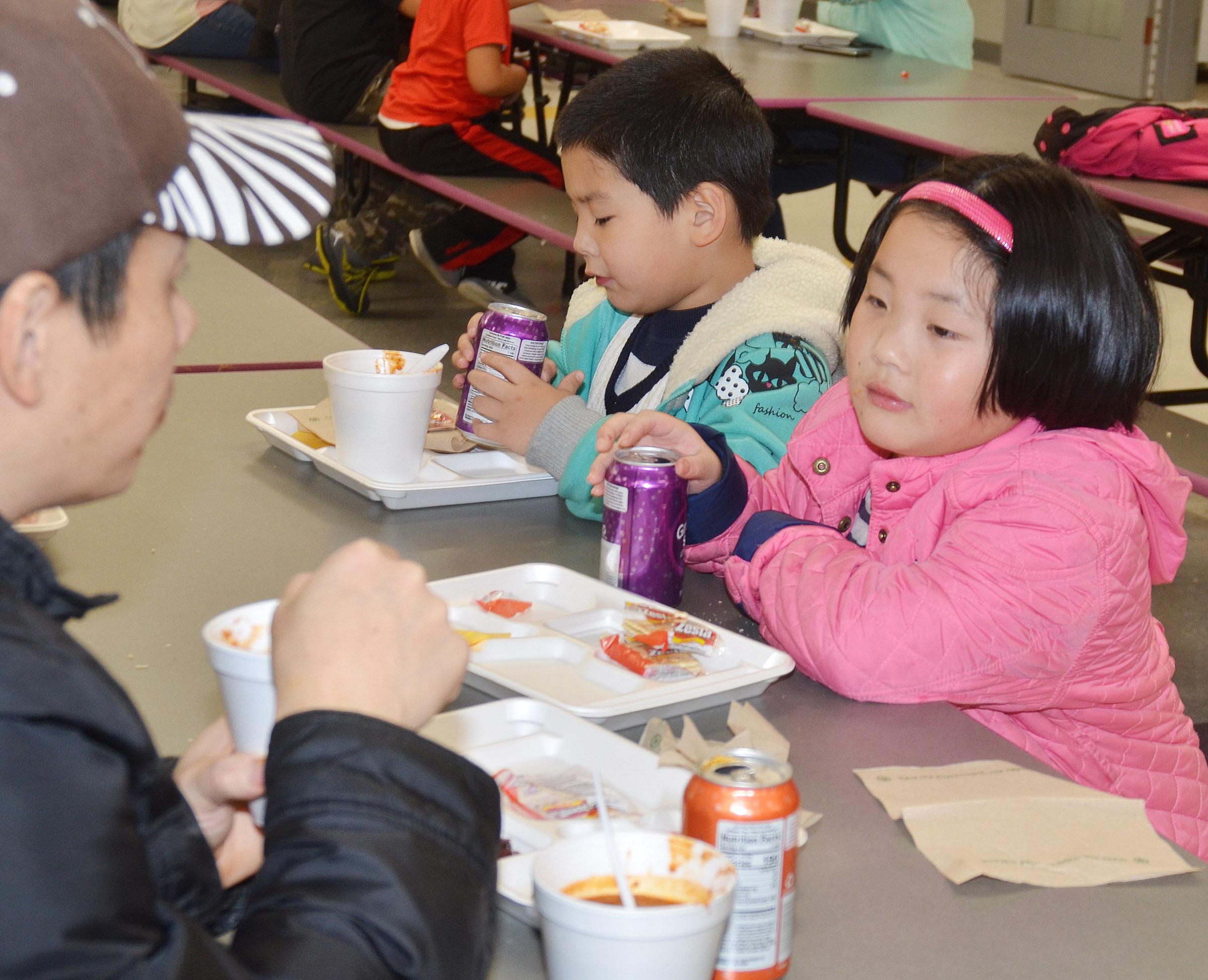 CES kindergartener William Li, at left, and his sister, first-grader Vicky Li, enjoy chili with their father, Xiao Li.