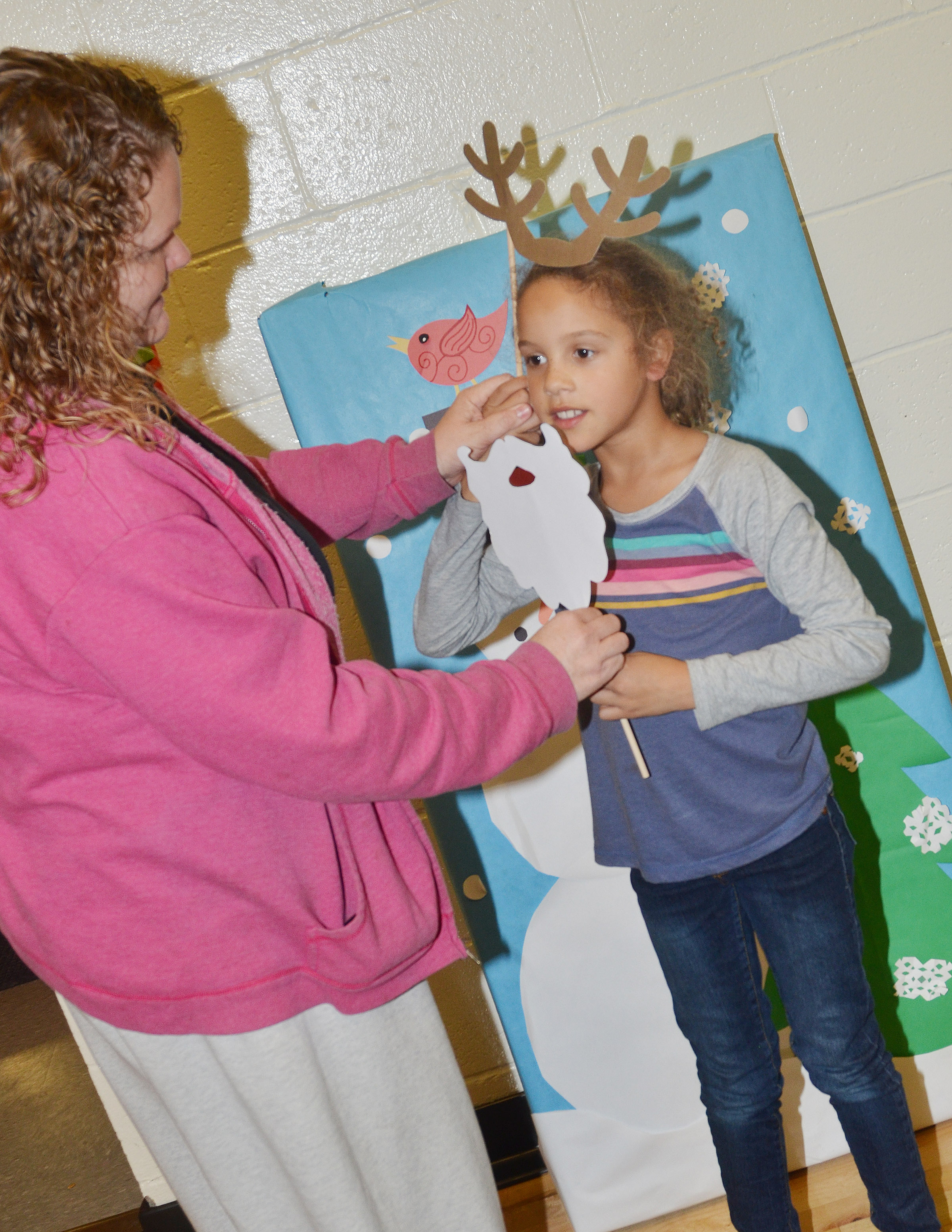 CES second-grader Keiava Thompson gets ready to pose for a photo, with some help from her mother, Tammy Pittman.