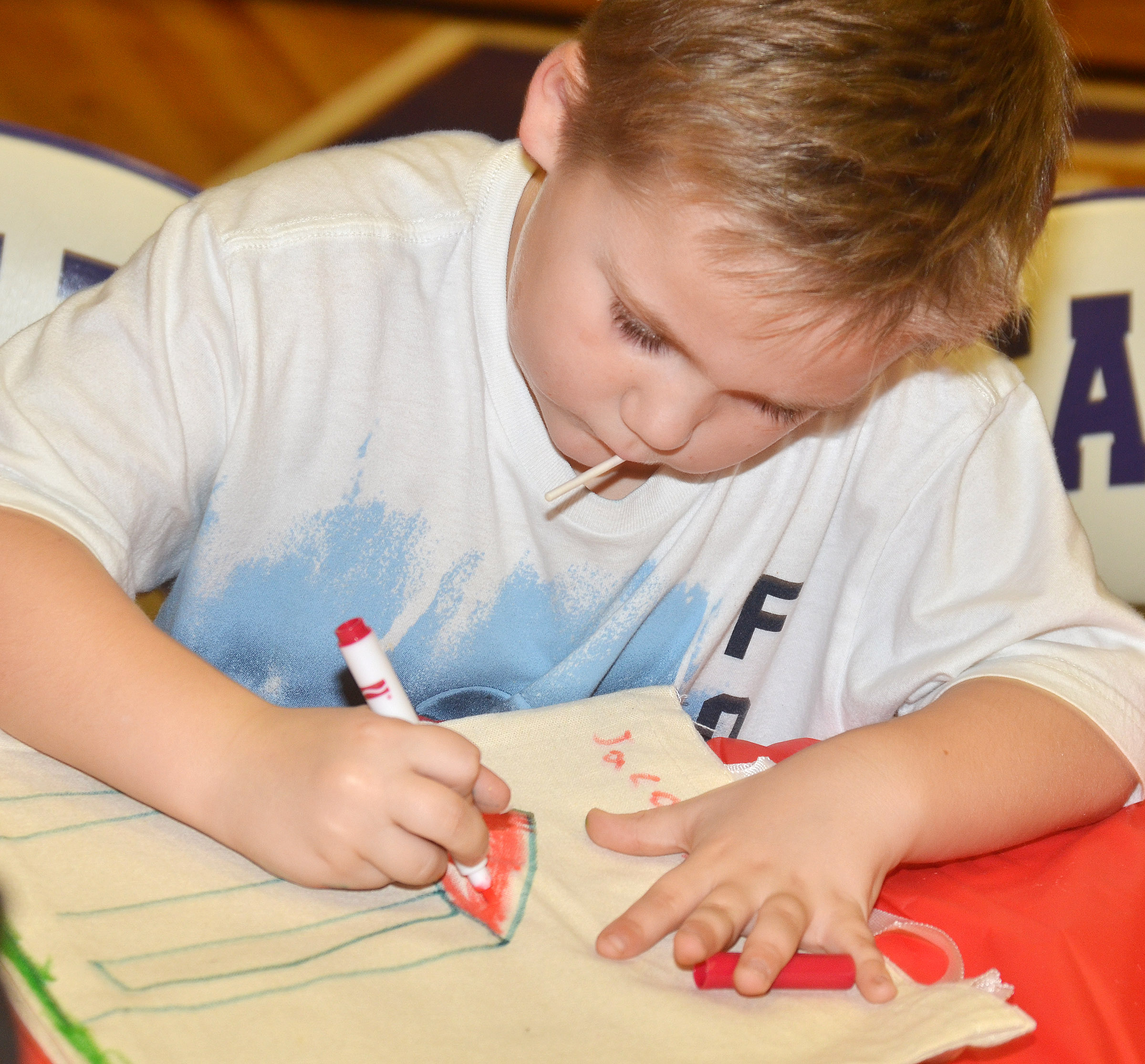 CES kindergartener Jacob Sandidge decorates a tote bag.