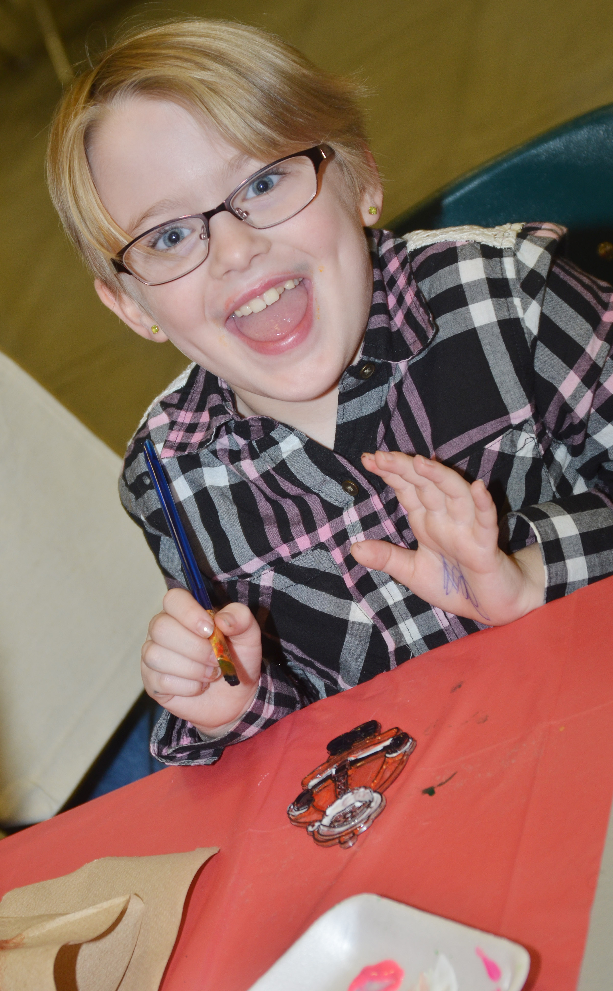 CES second-grader Maddie Brunelle smiles as she paints an ornament.