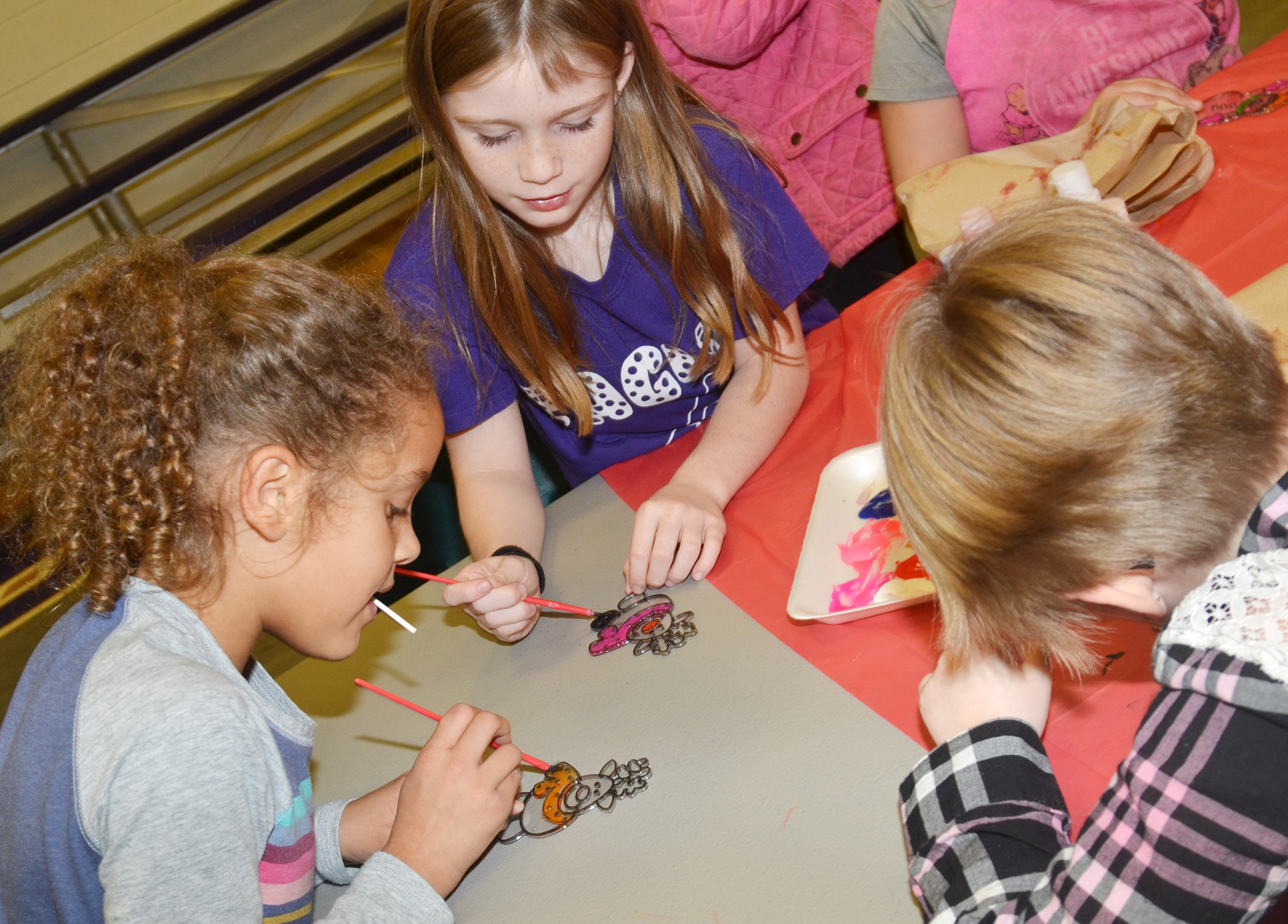 From left, CES second-graders Keiava Thompson, Izzy Brunelle and Maddie Brunelle paint ornaments.