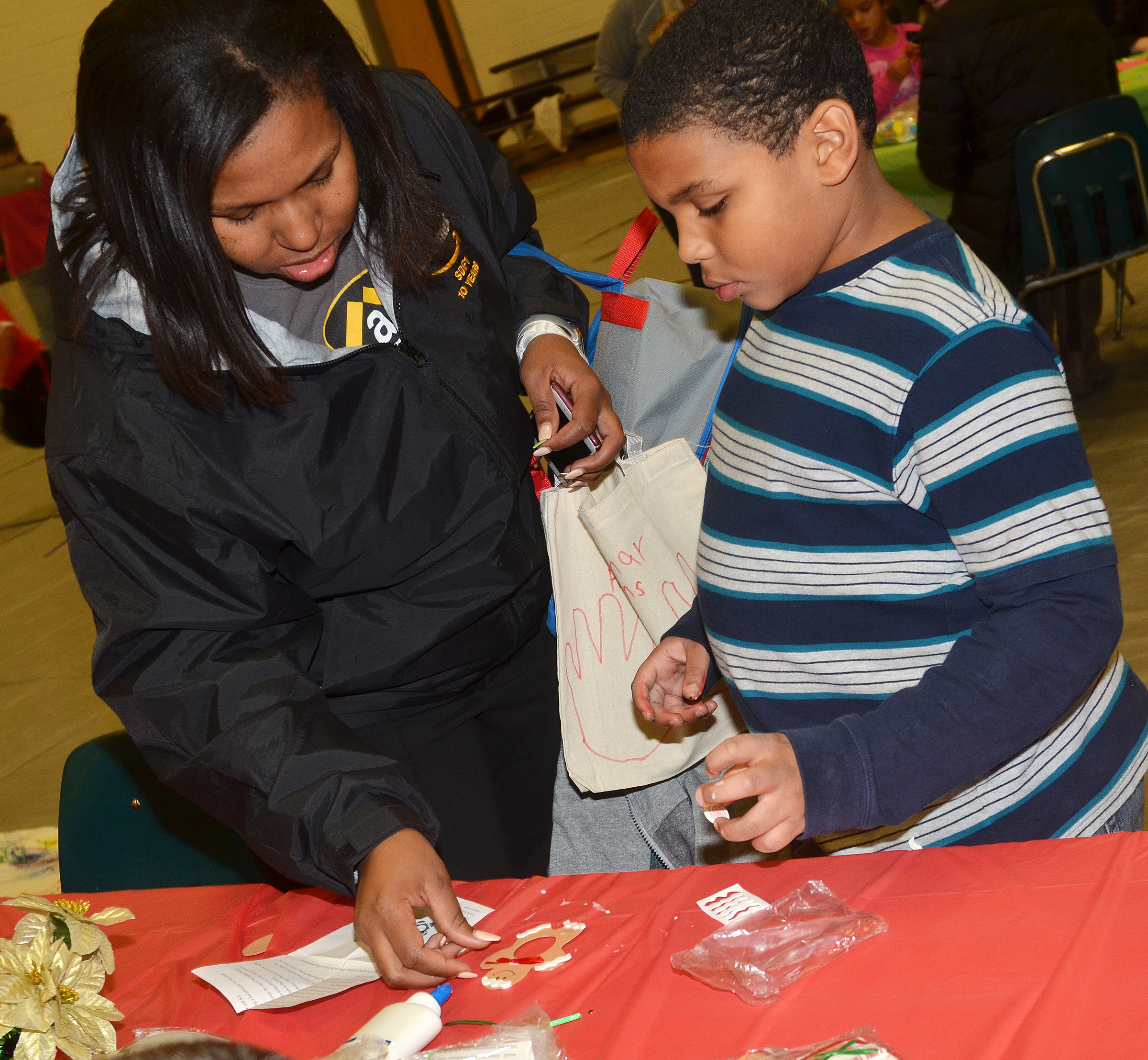 CES third-grader Zaemar Hoskins decorates an ornament with his mother, Jessica Douglas.