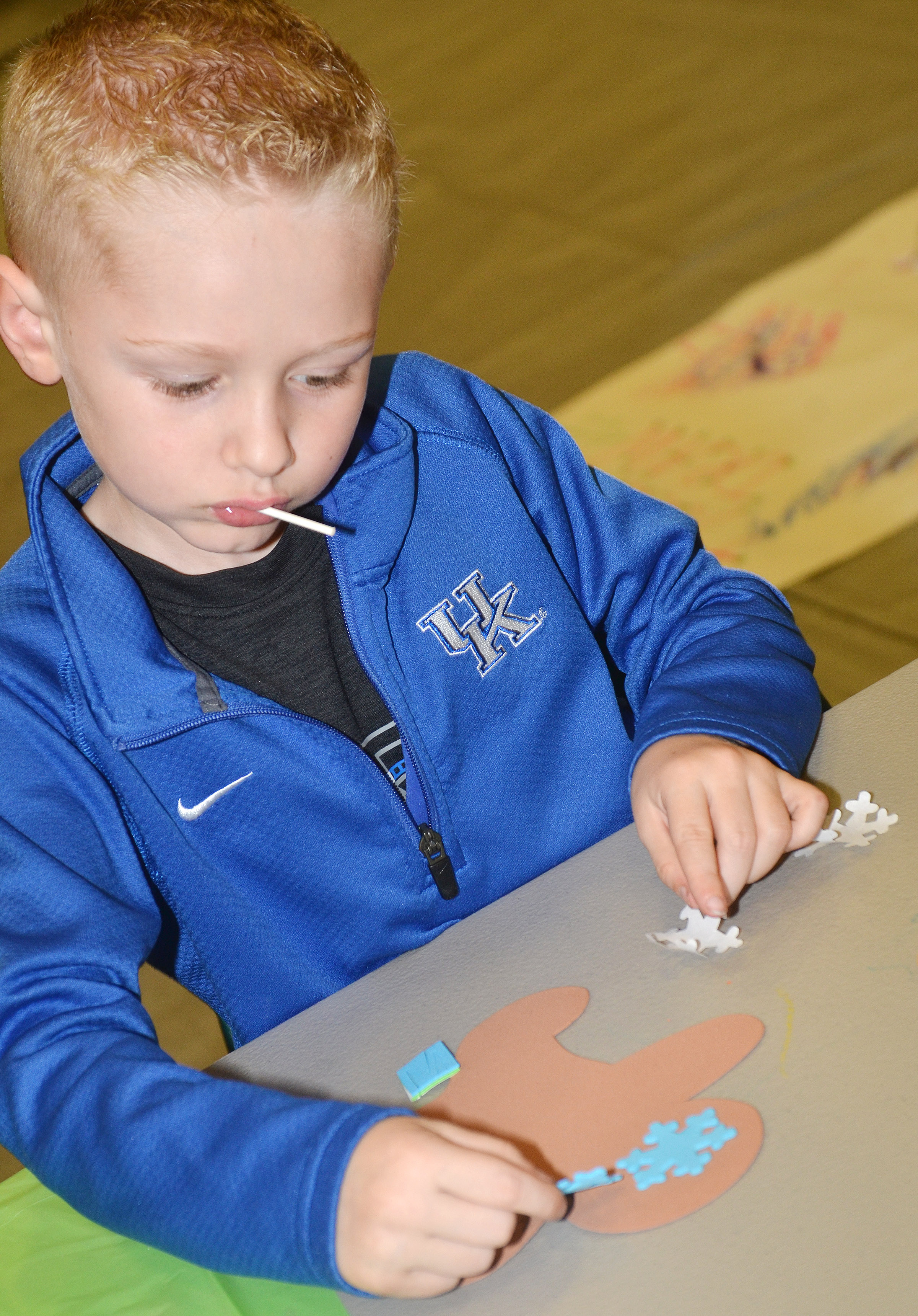 CES first-grader Jackson Wright decorates a gingerbread man.