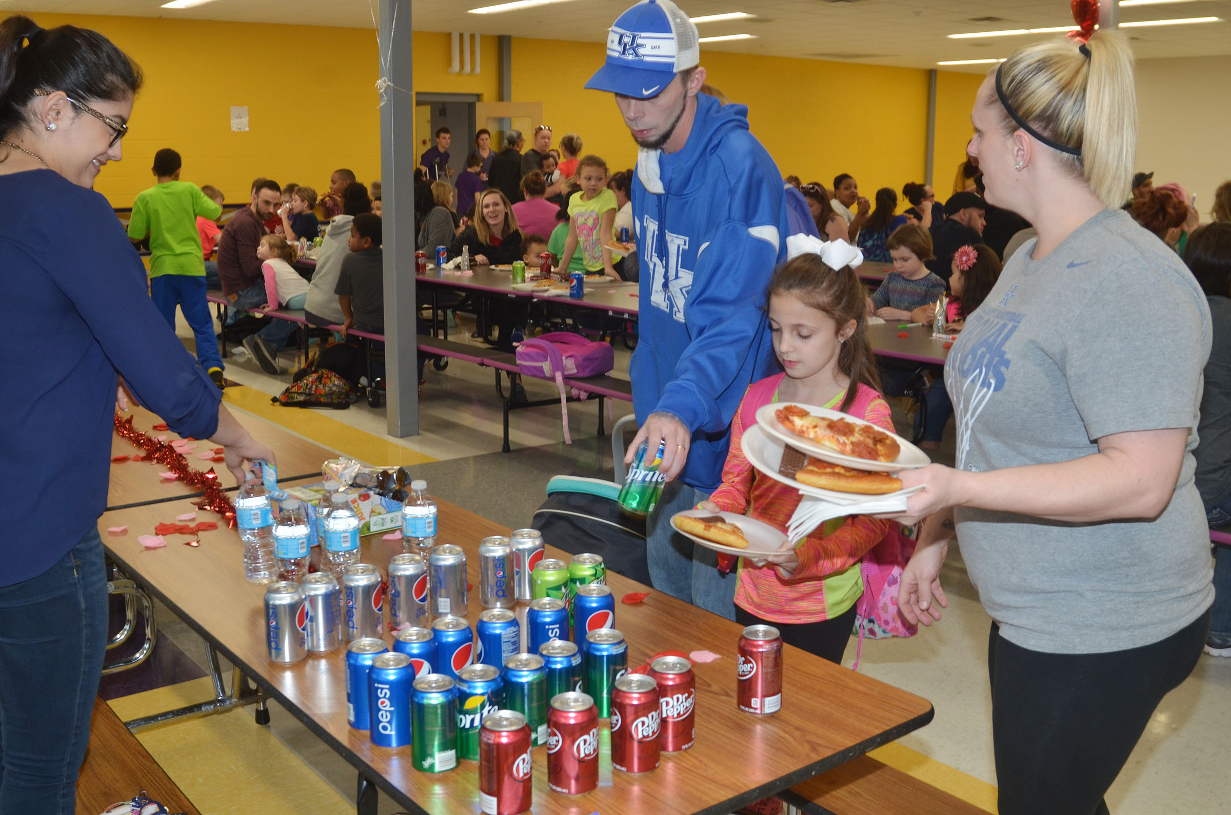 CES first-grader Lillian Martin and her parents, Danielle and Richard, are served pizza and soft drinks.
