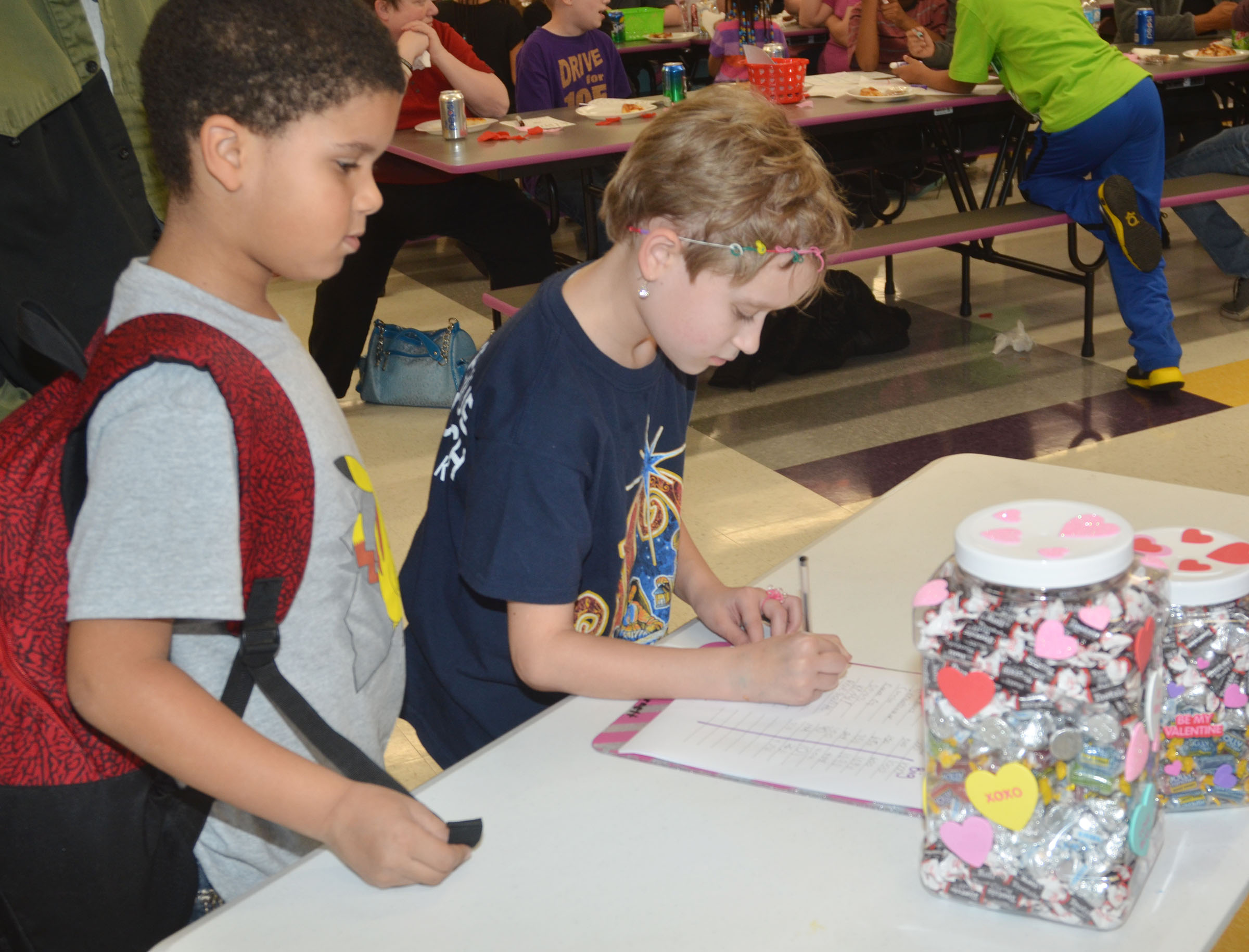 CES first-grader Navon Copeland, at left, and third-grader Katie Nunn guess how many pieces of candy are in a box.