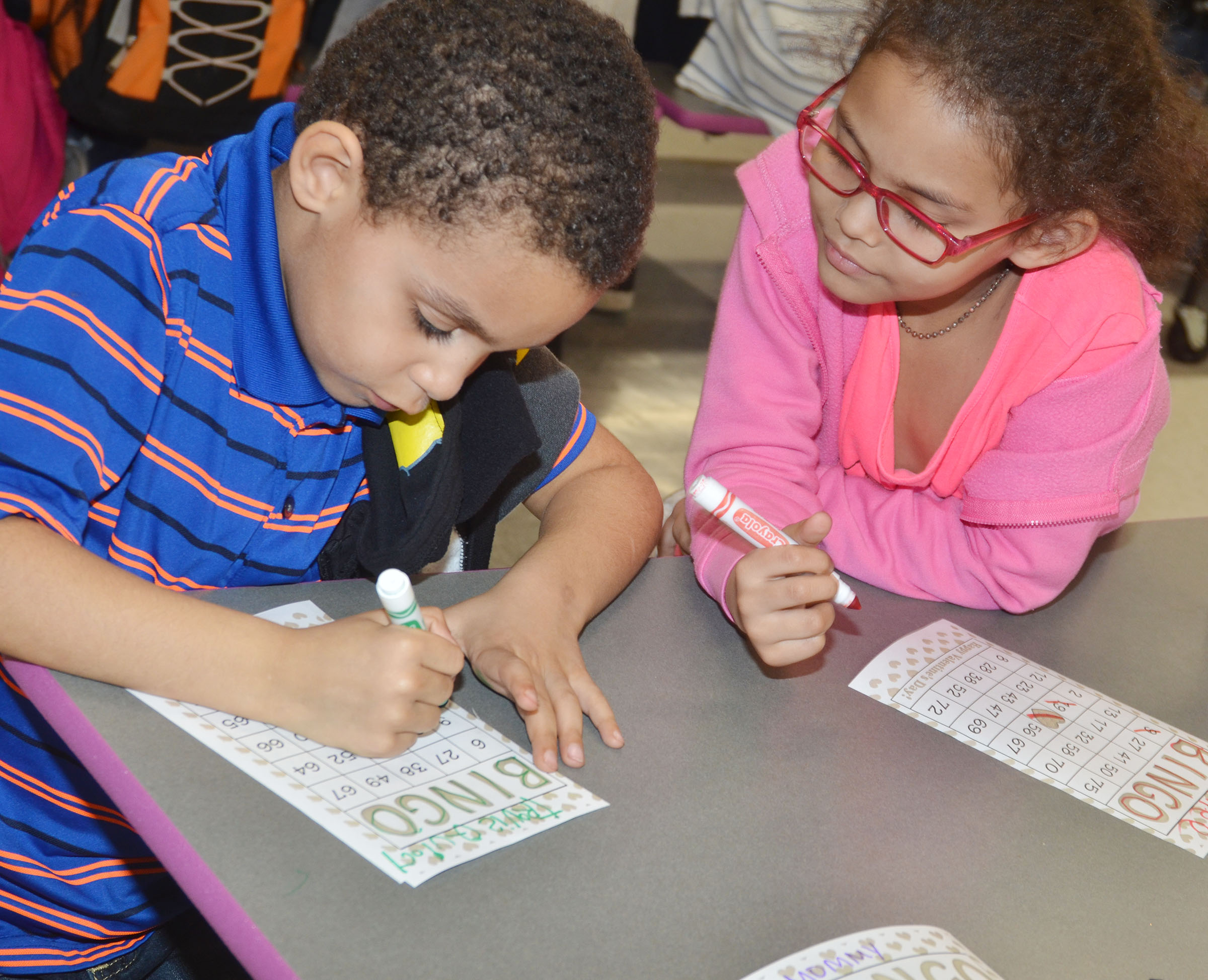 CES kindergarteners Quincy Travis, at left, and Marlee Dickens play math bingo.