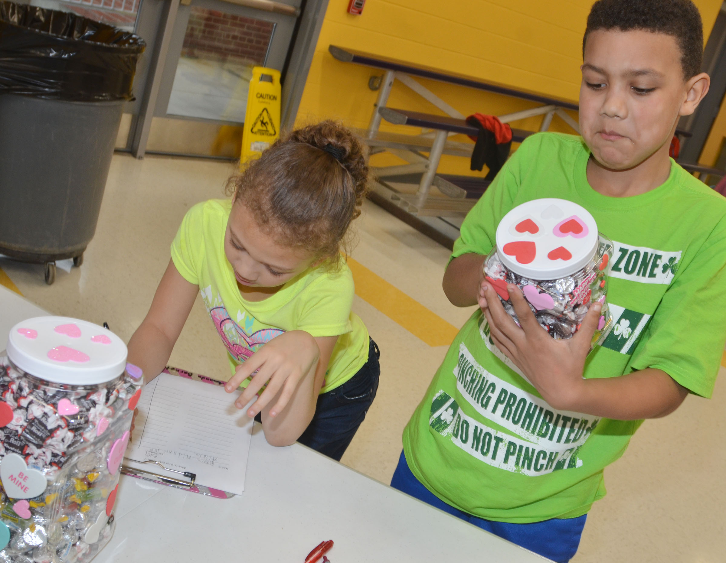 CES third-graders Alicia Spaulding, at left, and Christian Hart guess how many pieces of candy are in a box.