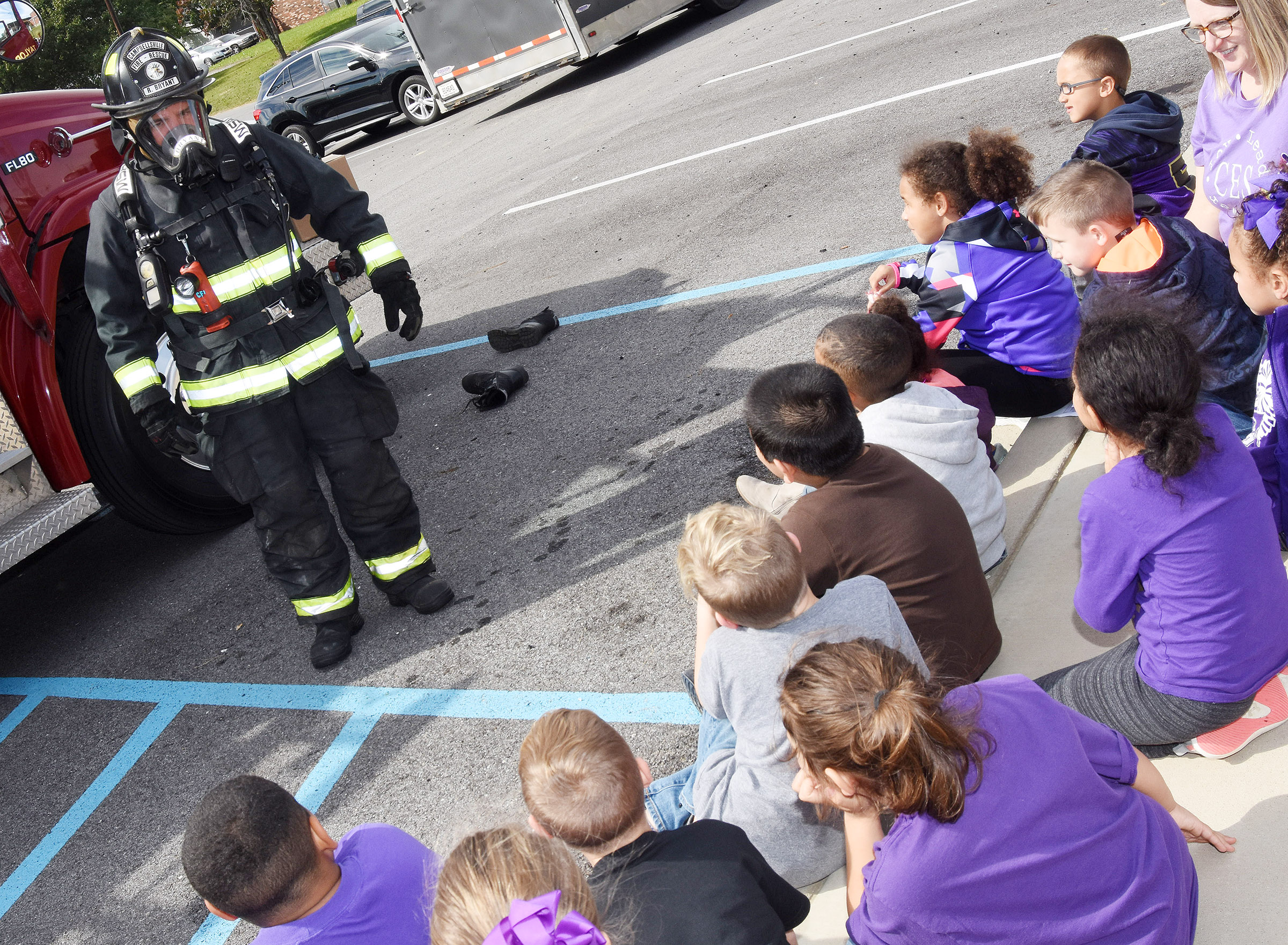 Robby Bryant, who works at Campbellsville Fire & Rescue and volunteers at Taylor County Fire Department, shows CES Wings Express students what a fire fighter looks like when wearing all of his or her equipment.