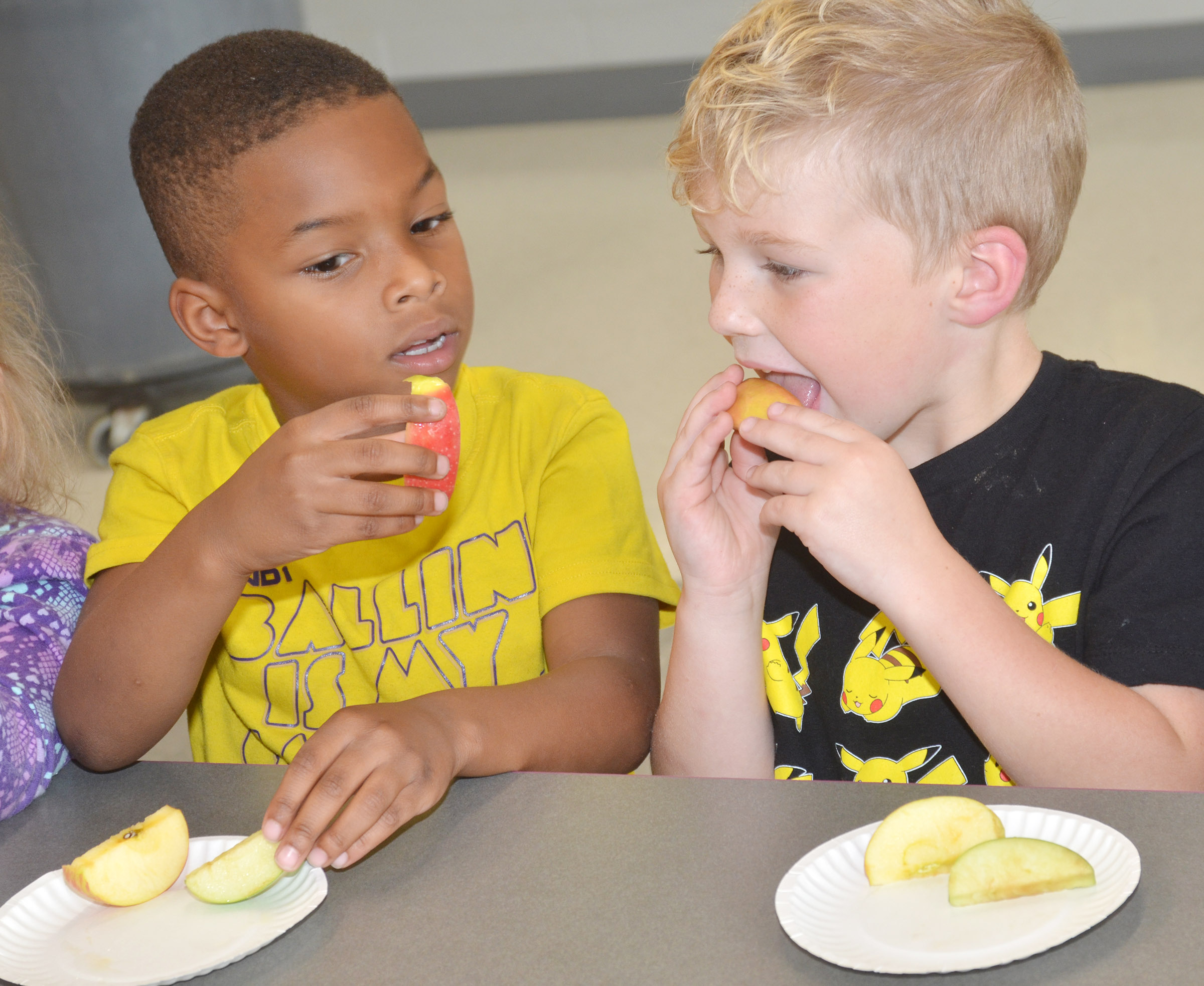 CES Wings Express kindergarten students Kaiyden Vancleave, at left, and Landry Brown sample different types of apples.