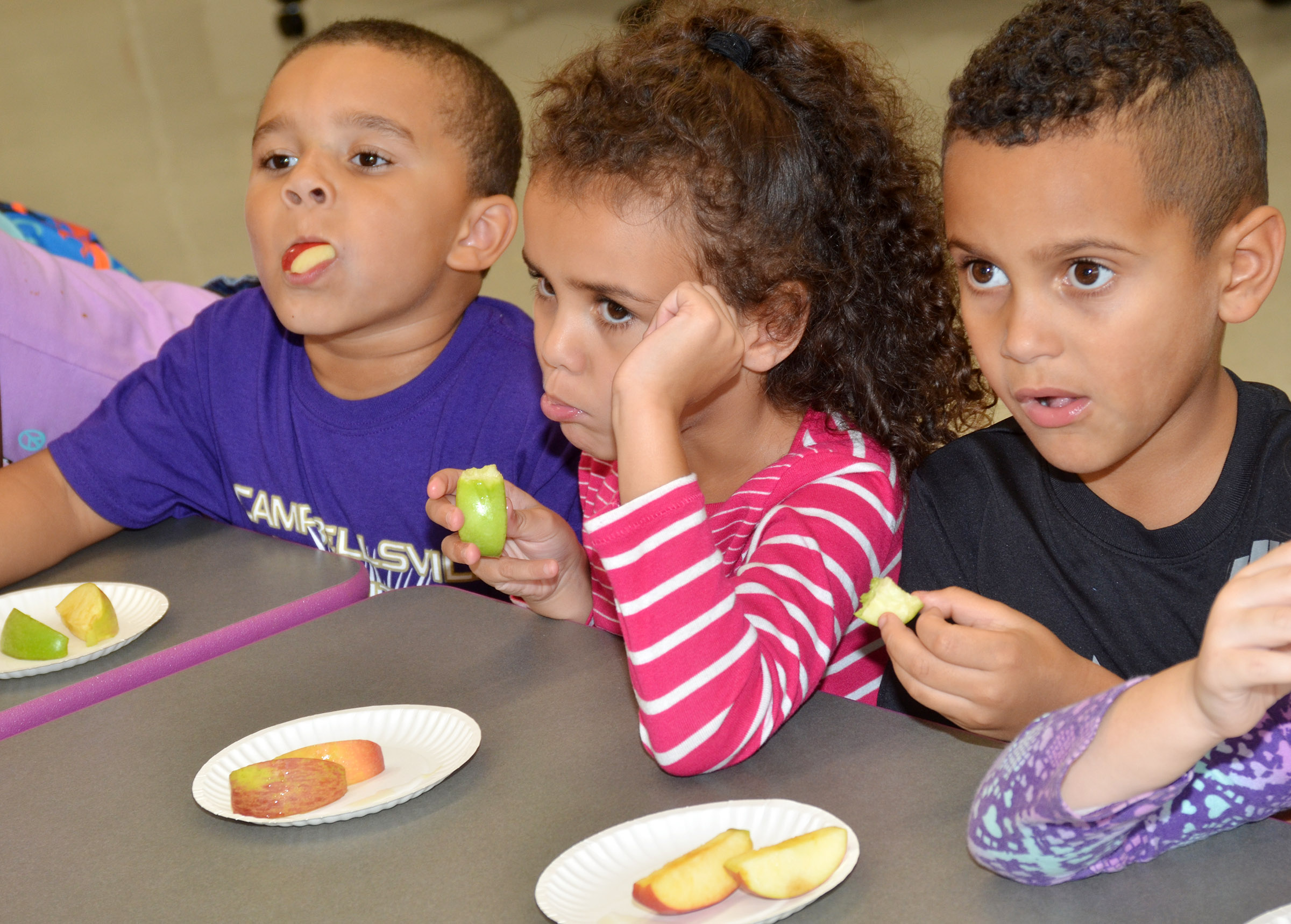 From left, CES Wings Express kindergarten students Tyrek Moore, Adelyn Litsey and Kingston Cowherd sample different types of apples.