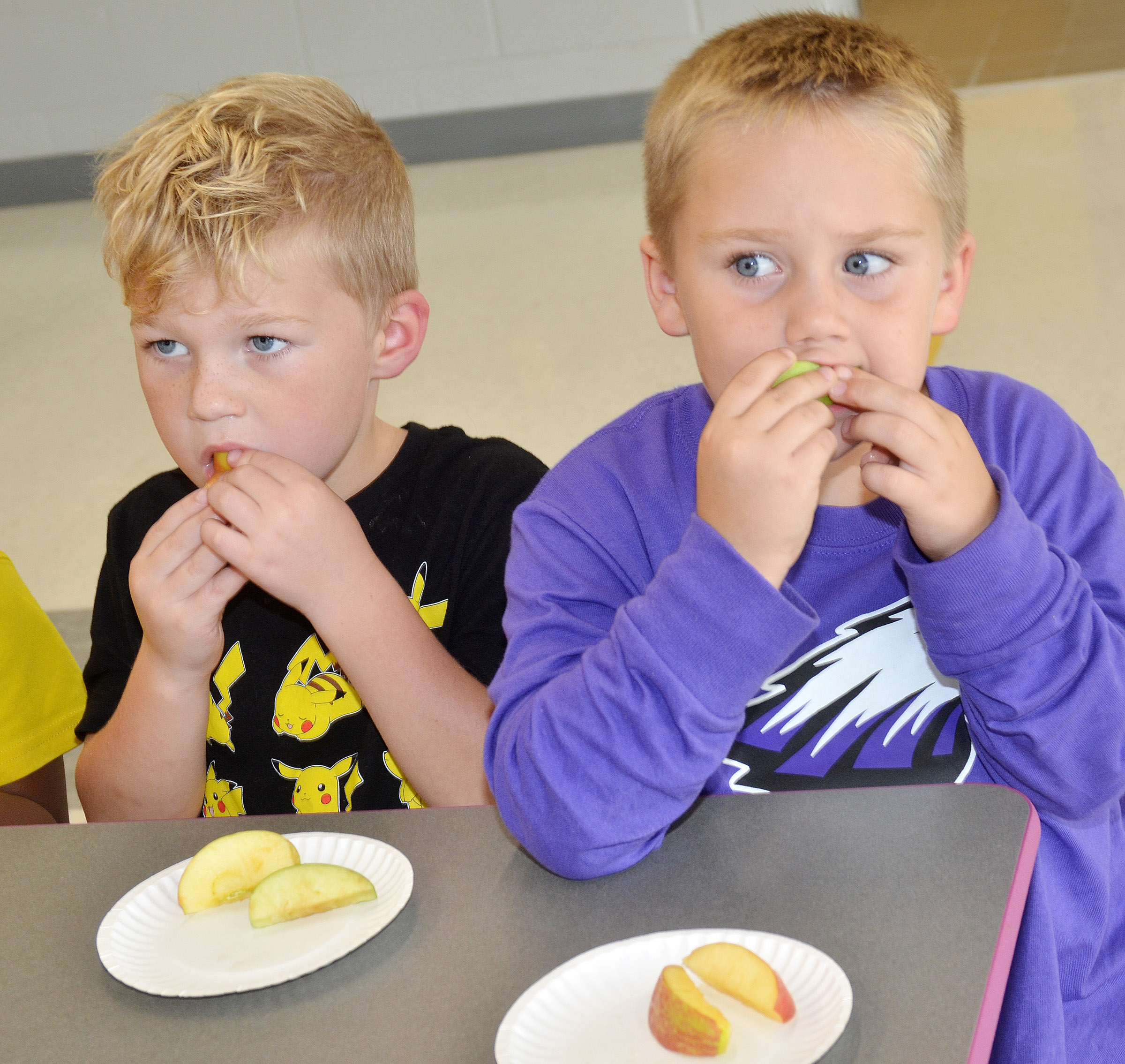 CES Wings Express kindergarten students Landry Brown, at left, and Jacob Sandidge sample different types of apples.