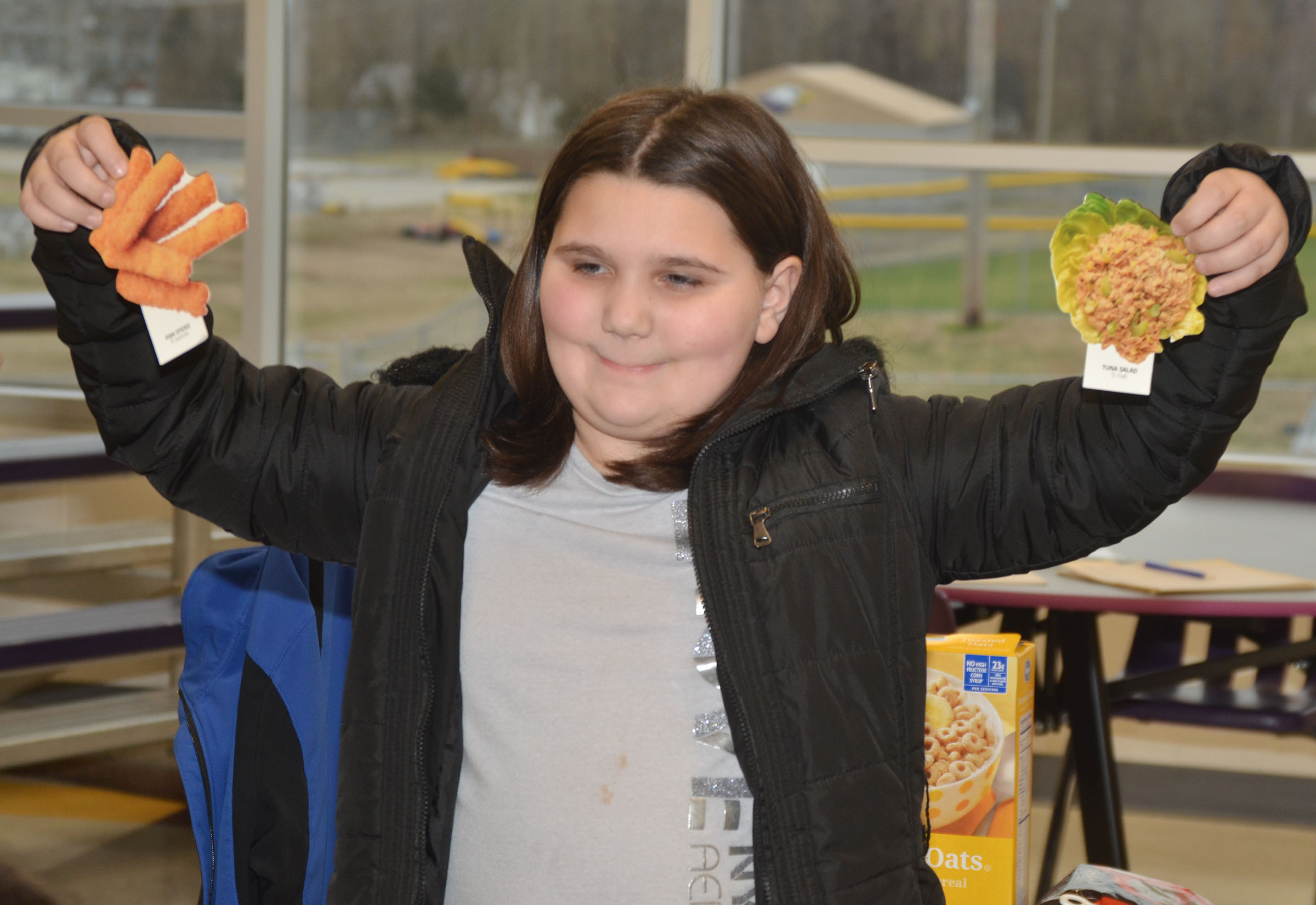 CES third-grader Kailei Hernandez asks her classmates which is healthier, cheese sticks or tuna fish.