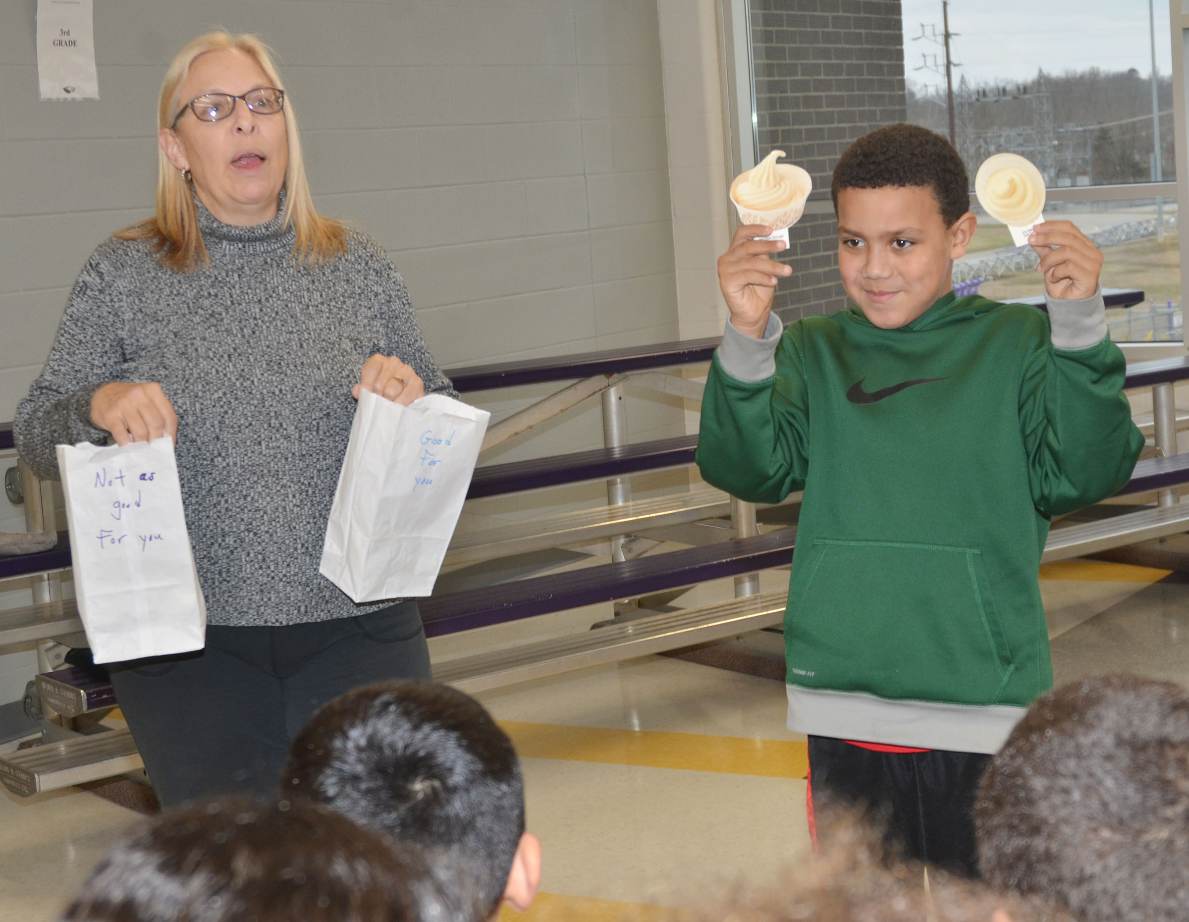CES third-grader Christian Hart and Angie Freeman, expanded foods and nutrition program assistant at Taylor County Extension Office, ask the group which is healthier, ice cream or frozen yogurt.