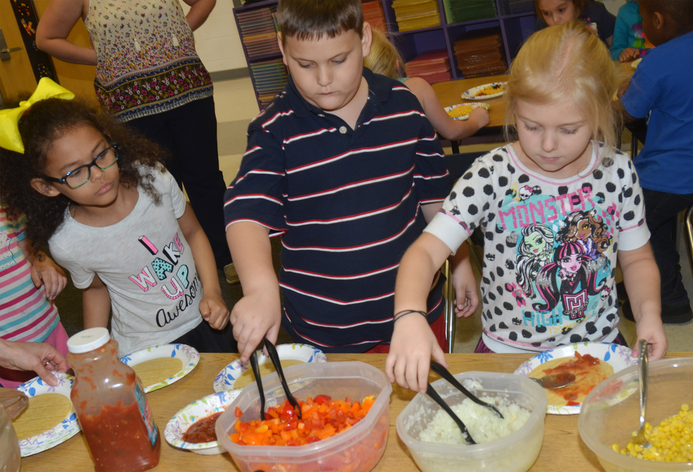 From left, CES kindergarteners Marlee Dickens, Cloud Malone and Aubrey Novak make their own Mexican pizzas.