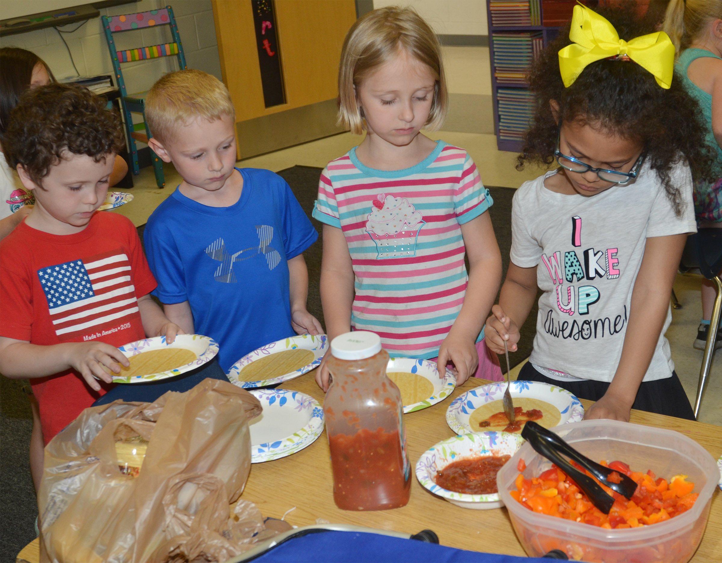 CES kindergarteners, from left, Braydan Dyer, Jackson Wright, LeeAnna Garvin and Marlee Dickens make their own Mexican pizzas.
